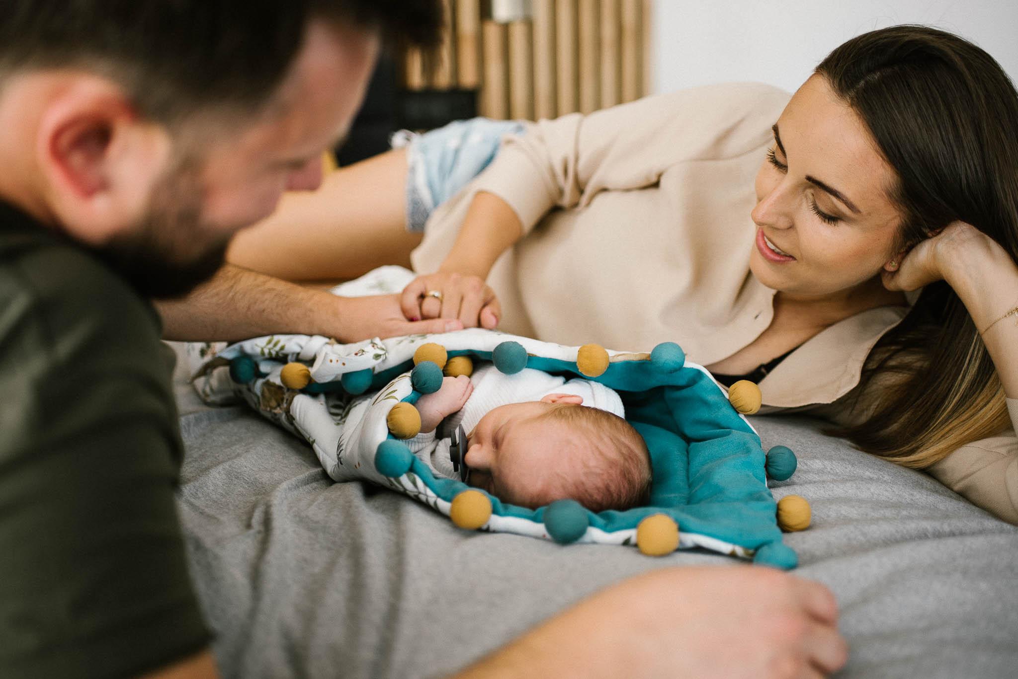 Rodzice leżą na łóżku i patrzą na noworodka - sesja noworodkowa lifestyle w Poznaniu