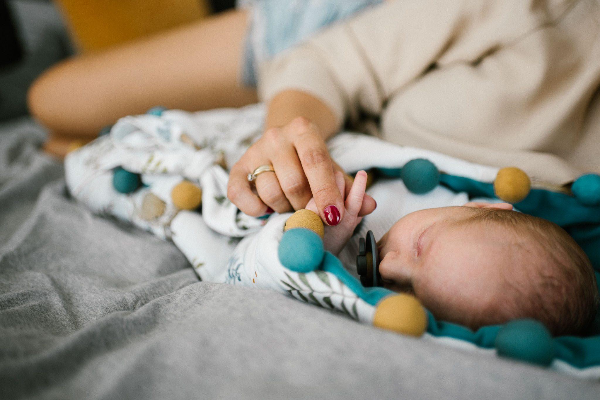 Mama trzyma noworodka za rączkę - sesja noworodkowa lifestyle w Poznaniu