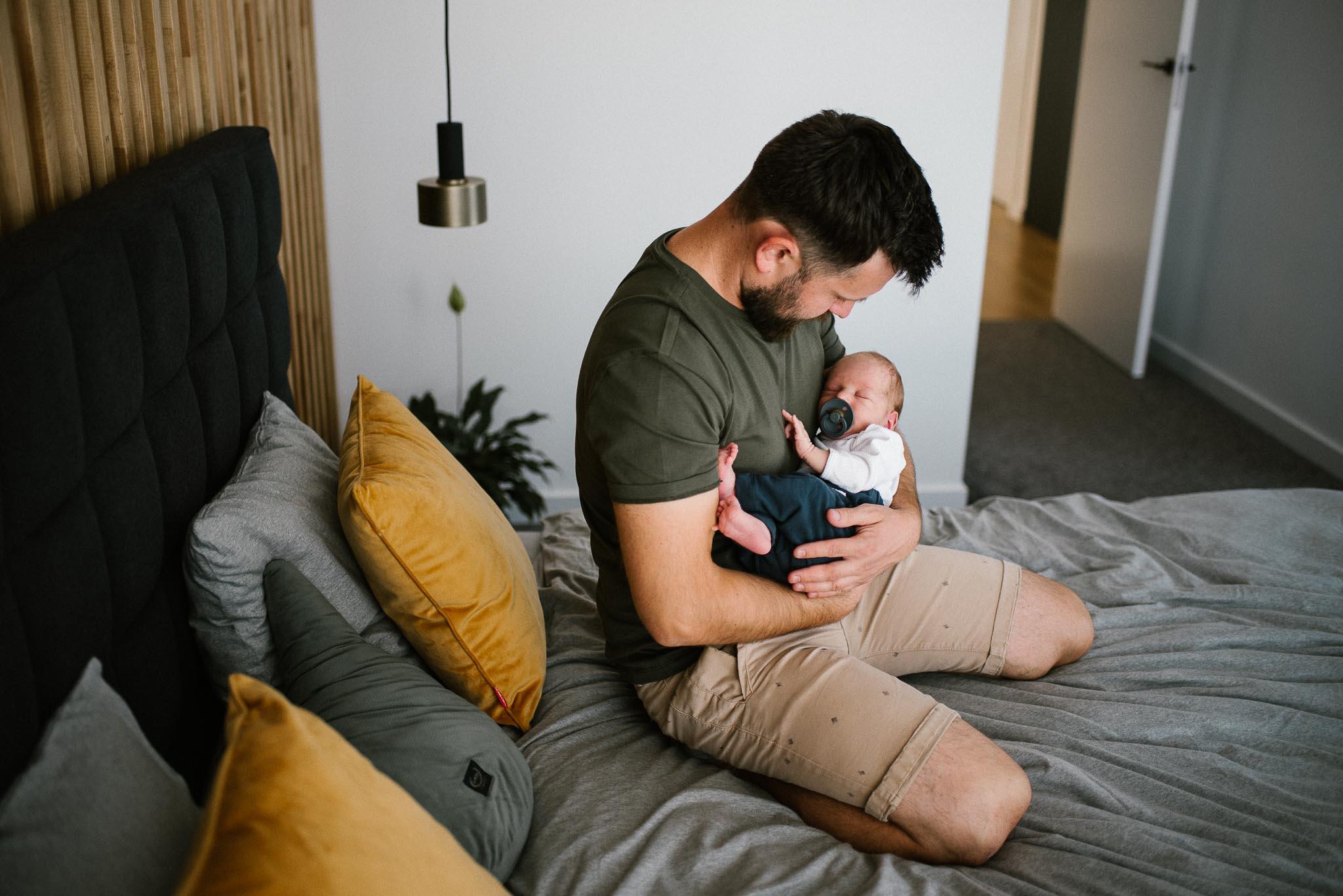 tata trzyma noworodka na rękach - sesja noworodkowa lifestyle w Poznaniu