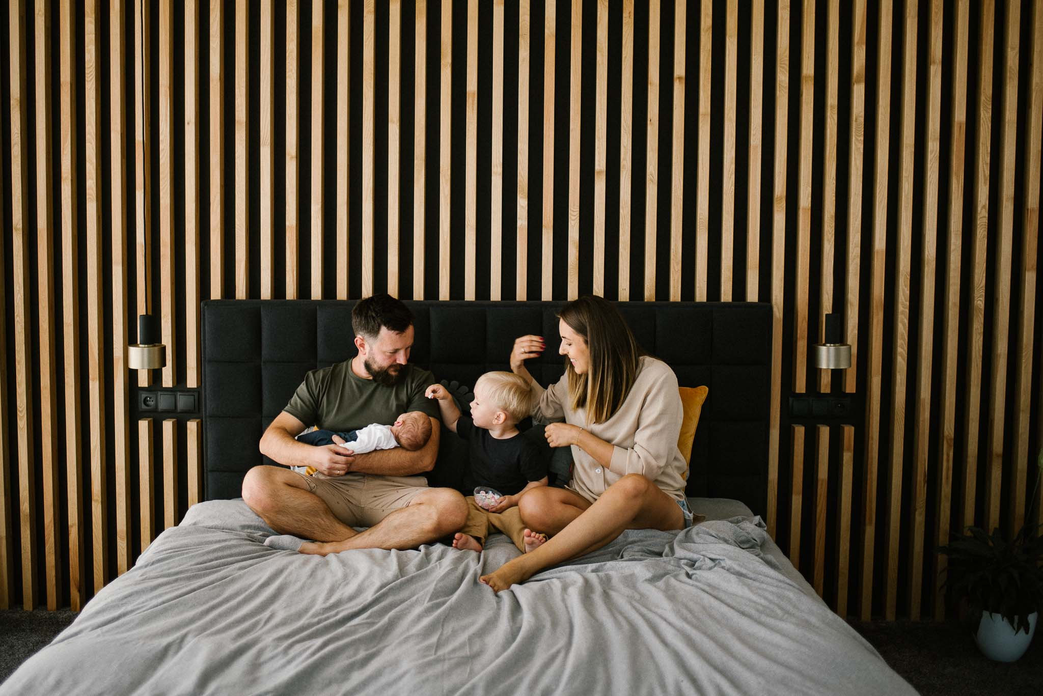 Rodzina siedzi na łóżku z niemowlakiem - sesja noworodkowa lifestyle w Poznaniu