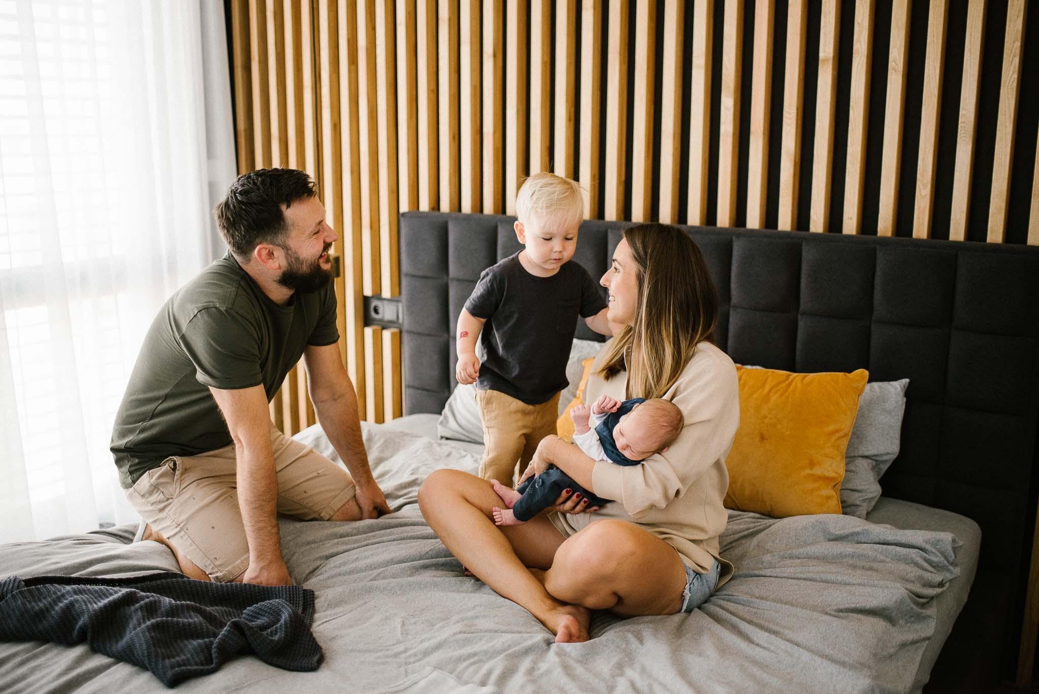 Rodzina z noworodkiem bawią się na łóżku -sesja noworodkowa lifestyle w Poznaniu
