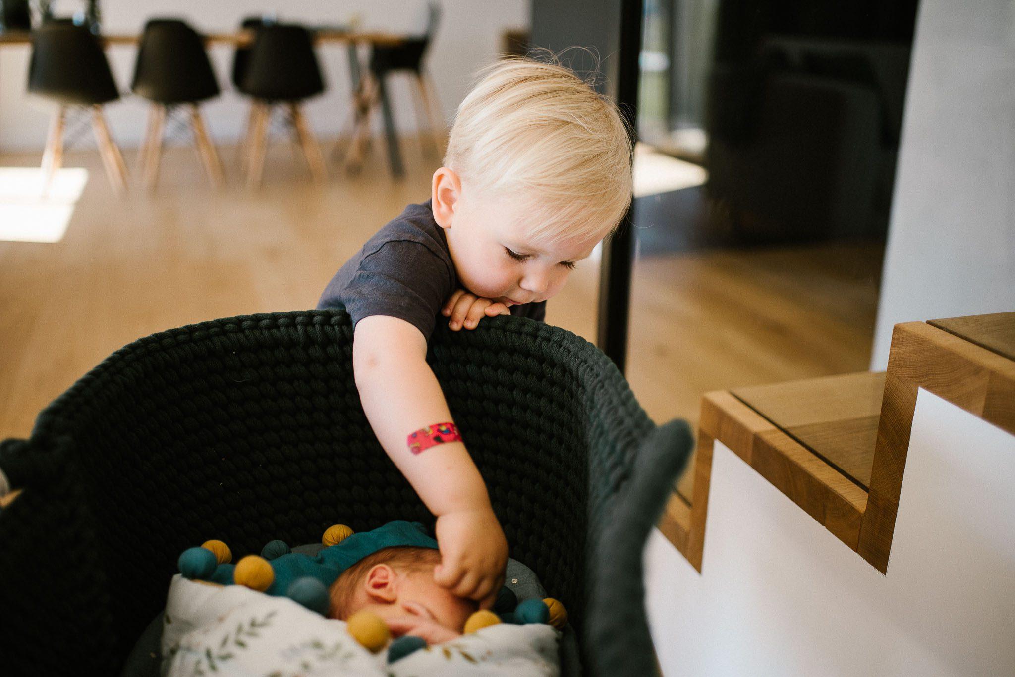 Chłopiec podchodzi do łóżeczka, w którym leży noworodek - sesja noworodkowa lifestyle w Poznaniu