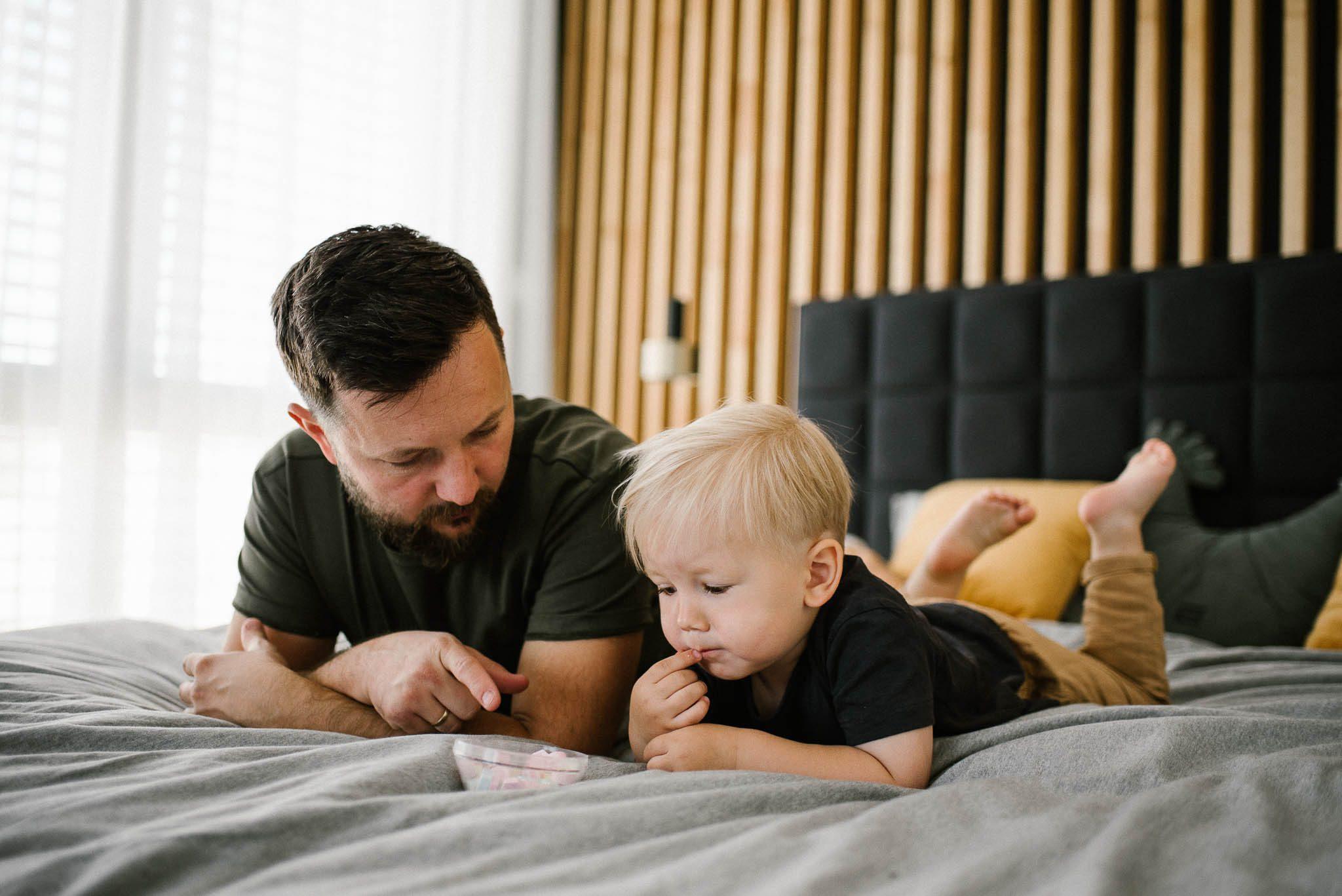 Tata z chłopcem leżą na łóżku - sesja noworodkowa lifestyle w Poznaniu