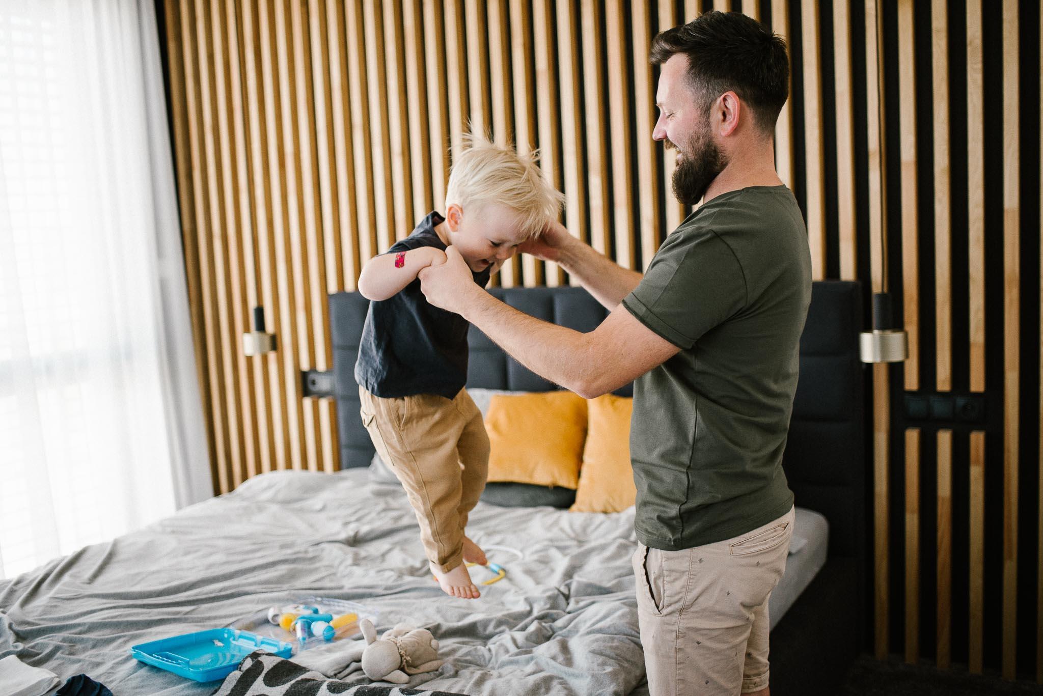 tata z synkiem skaczą po łóżku - sesja noworodkowa lifestyle w Poznaniu