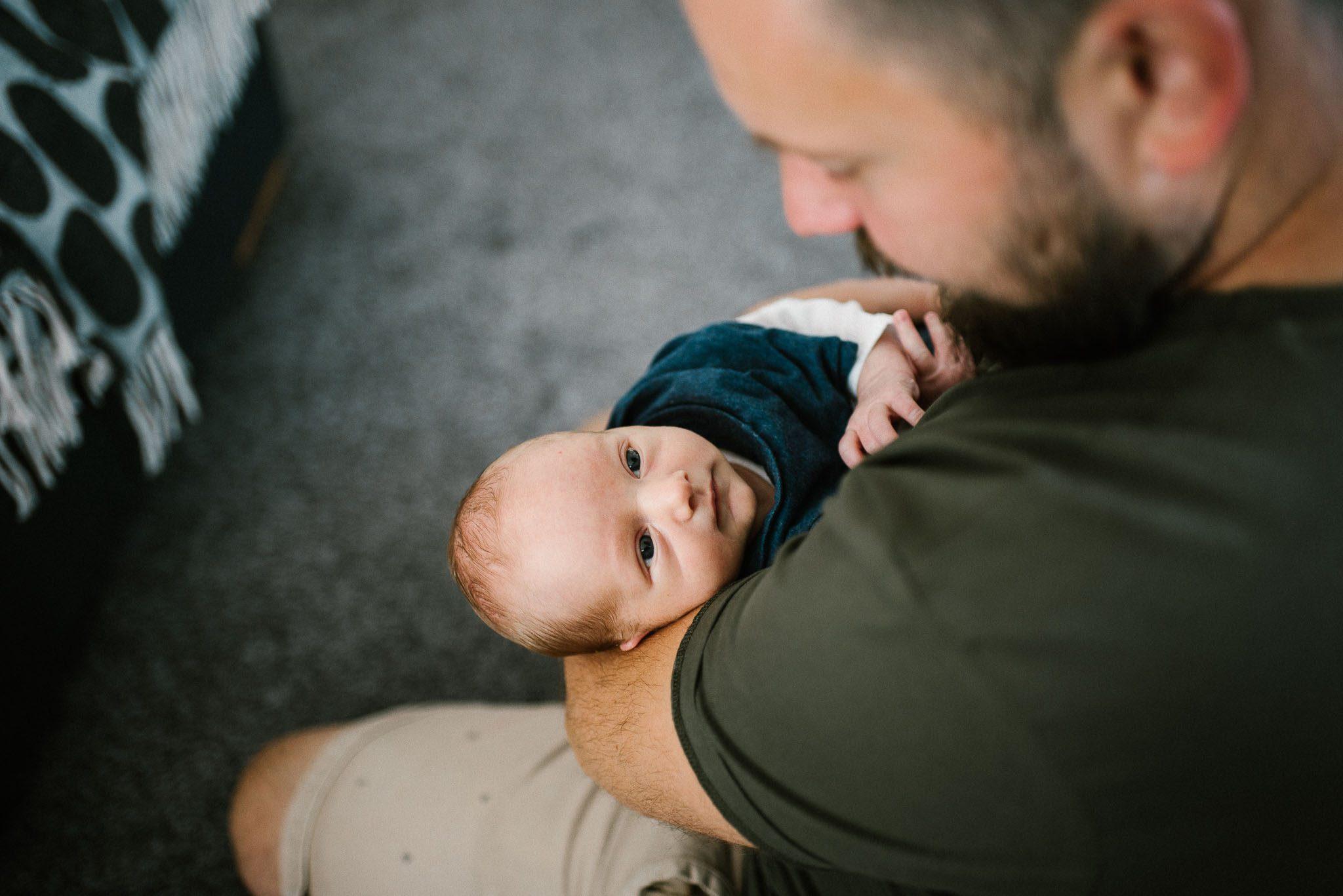 Tata trzyma noworodka na rękch - sesja noworodkowa lifestyle w Poznaniu