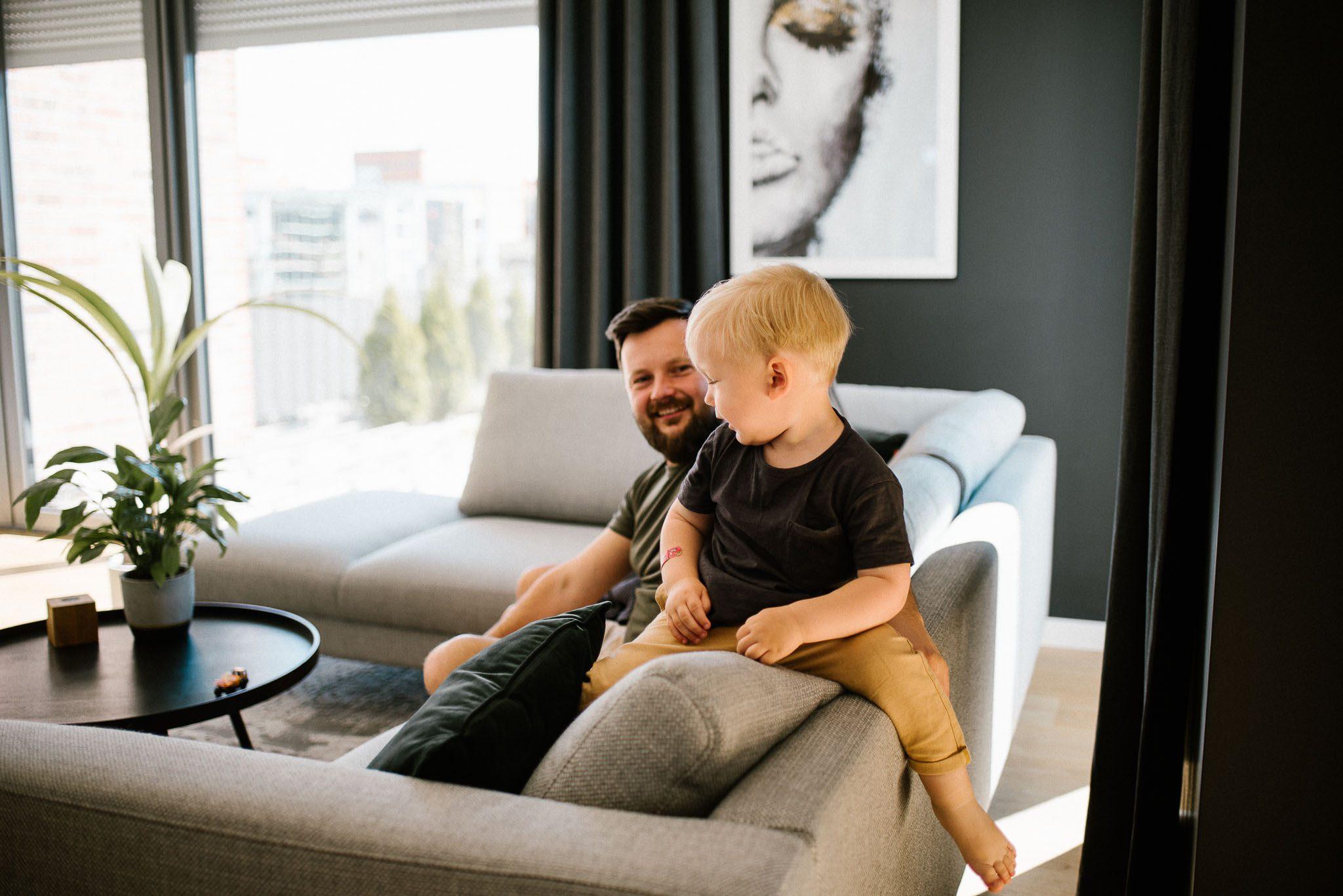 Chłopiec bawi się z tatą na kanapie - sesja noworodkowa lifestyle w Poznaniu