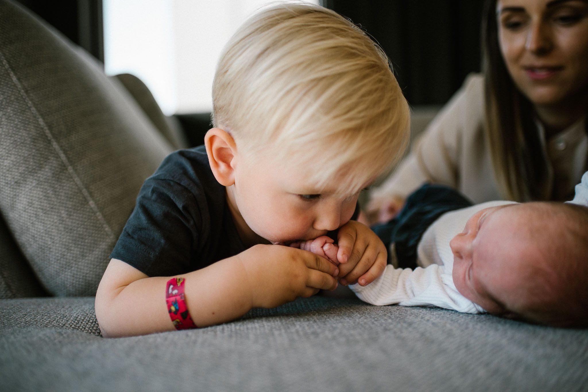 Chłopiec całuje rączkę noworodka - sesja noworodkowa lifestyle w Poznaniu