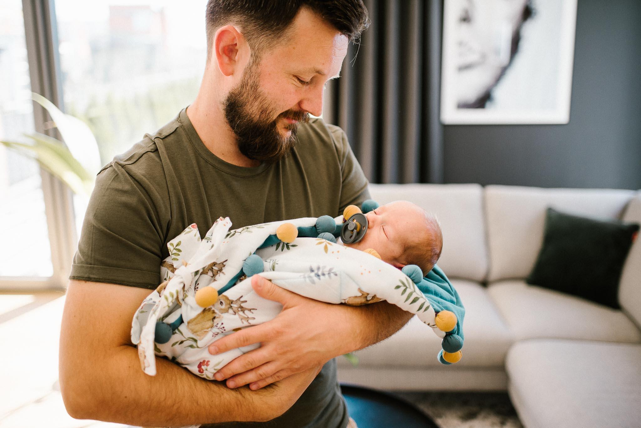 tata trzyma noworodka w rożku na rękach - sesja noworodkowa lifestyle w Poznaniu