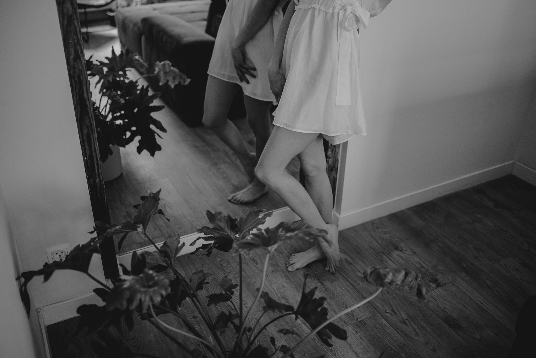 Kobieta stoi przed lustrem podczas sesji kobiecej i się przygląda, zbliżenie na nogi
