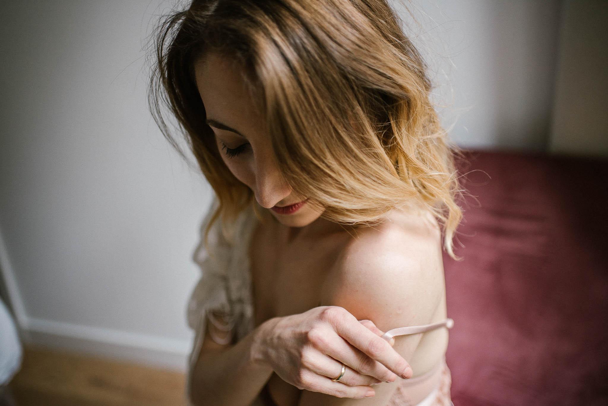 Kobieta zdejmuje ramiączko od stanika podczas zmysłowej sesji