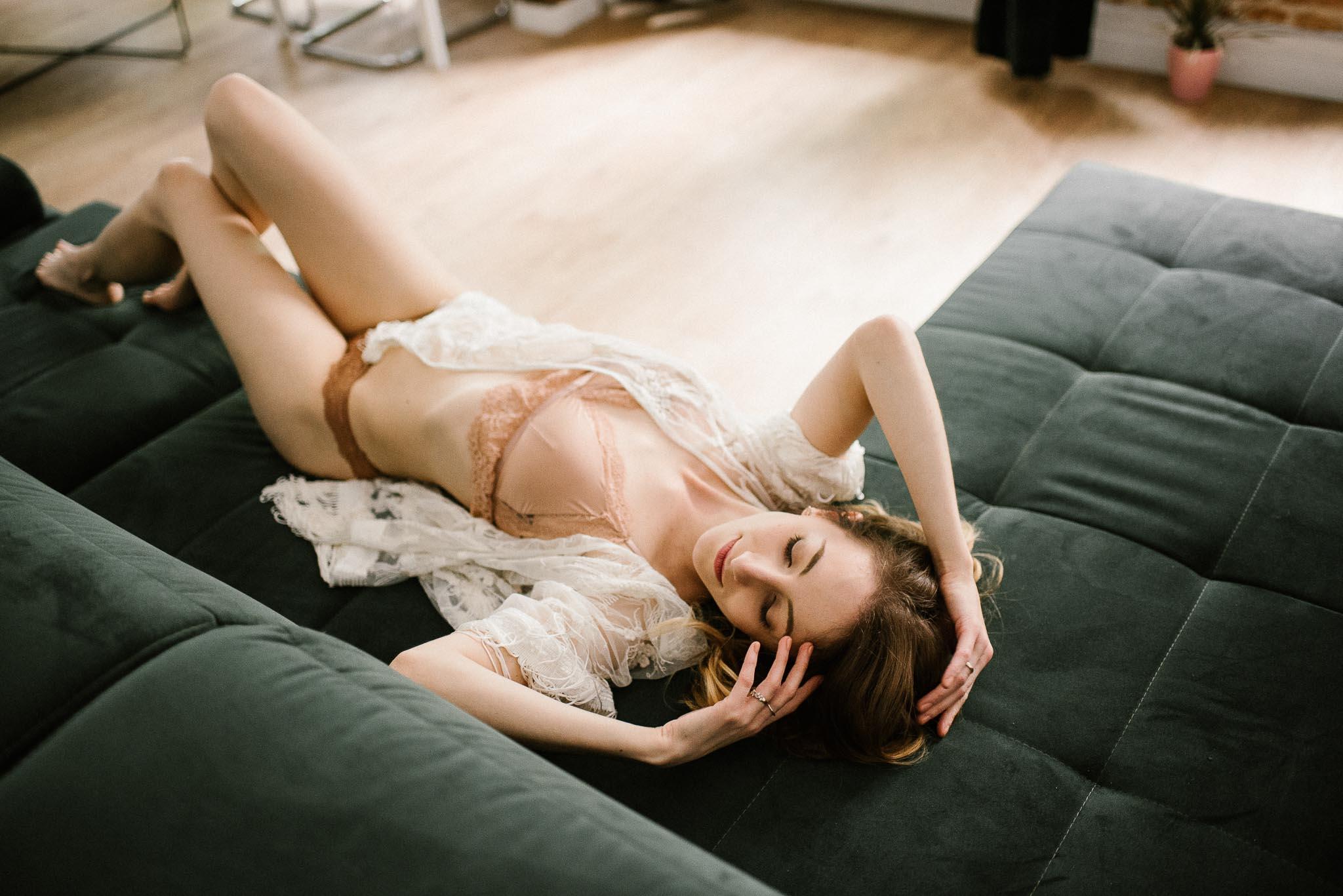 Kobieta w bieliźnie leży na łóżku w apartamencie