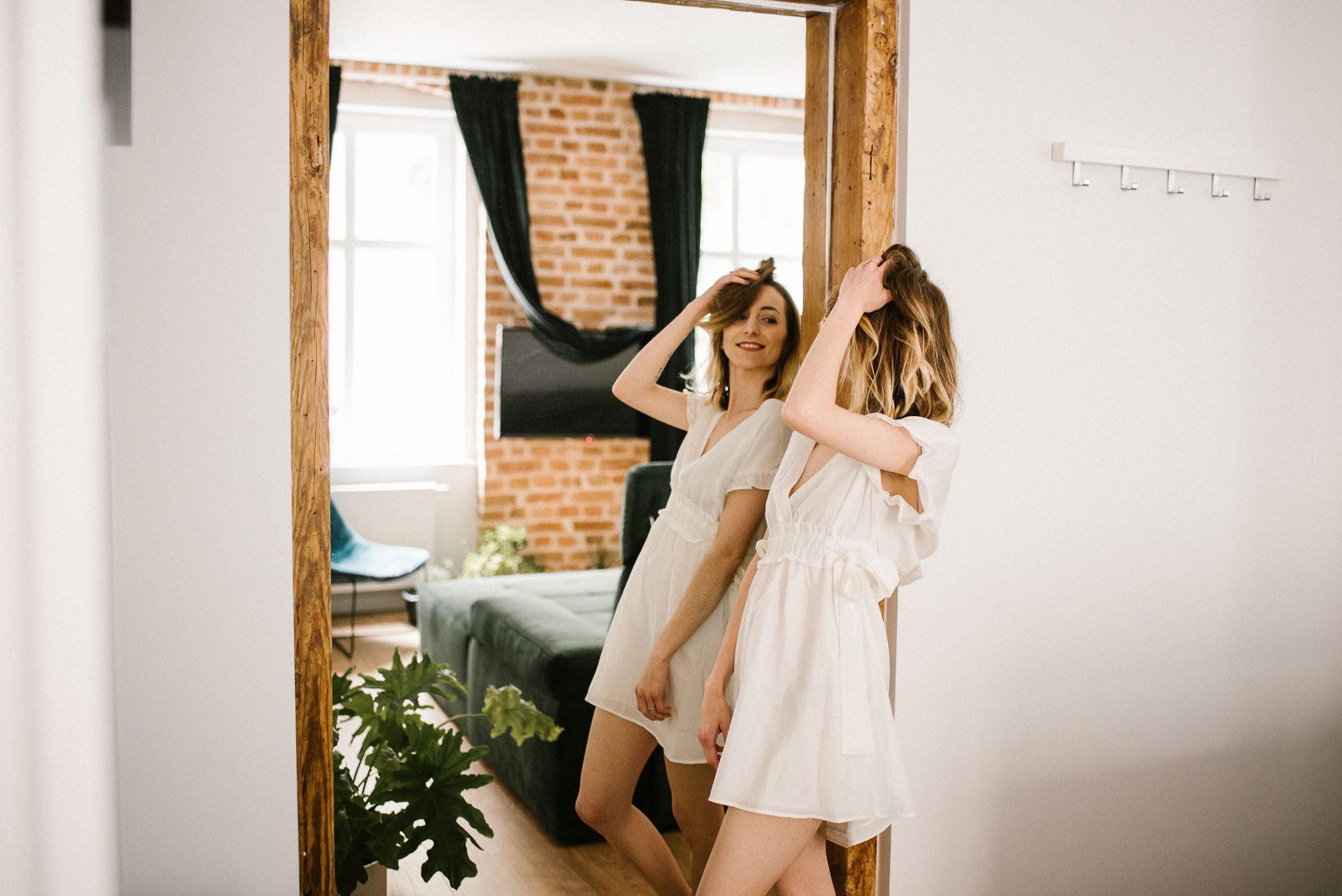 Kobieta podczas sesji kobiecej przegląda się w lustrze w apartamencie