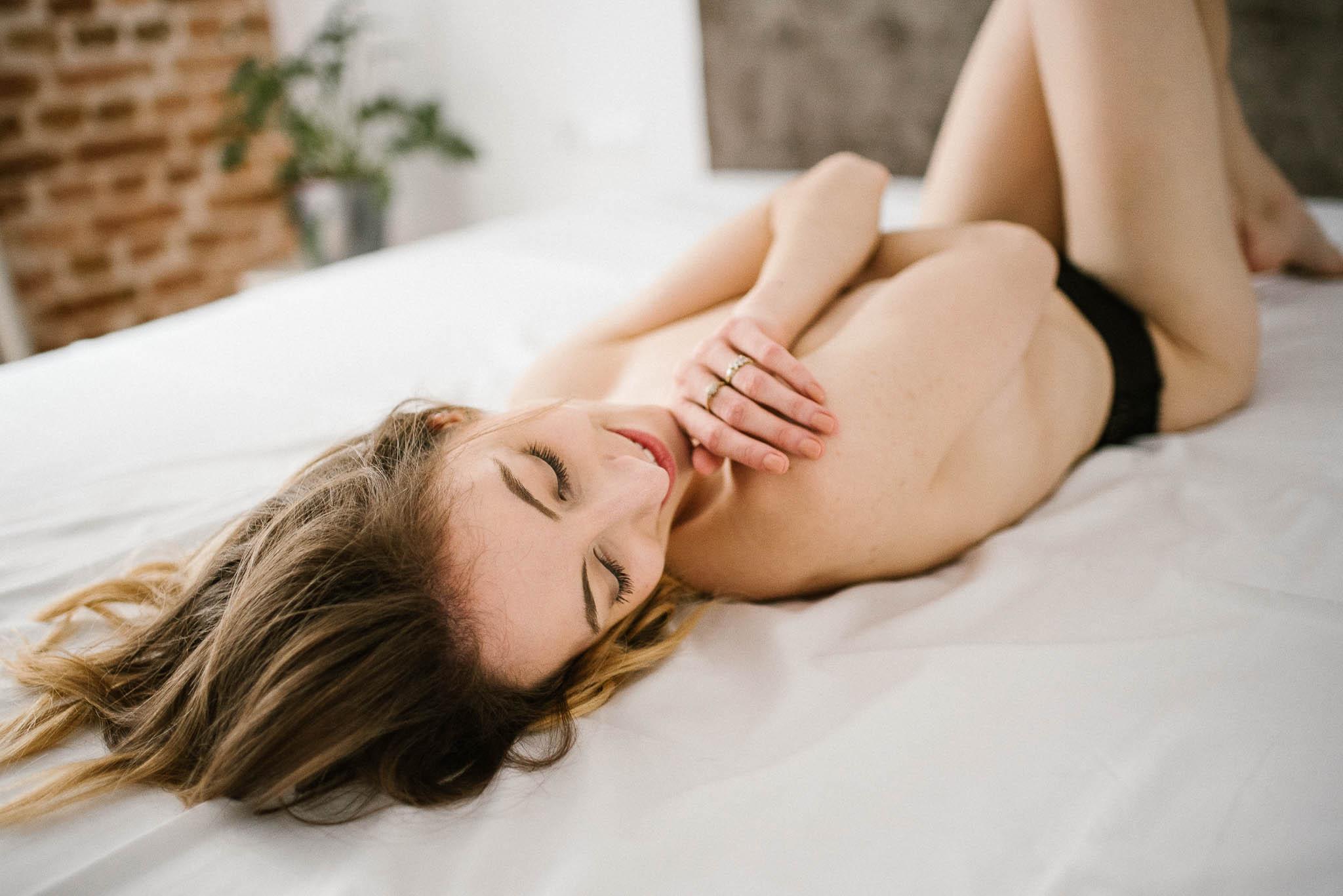 Kobieta w czarnej bieliźnie leży na łóżku - sesja kobieca w apartamencie w Poznaniu