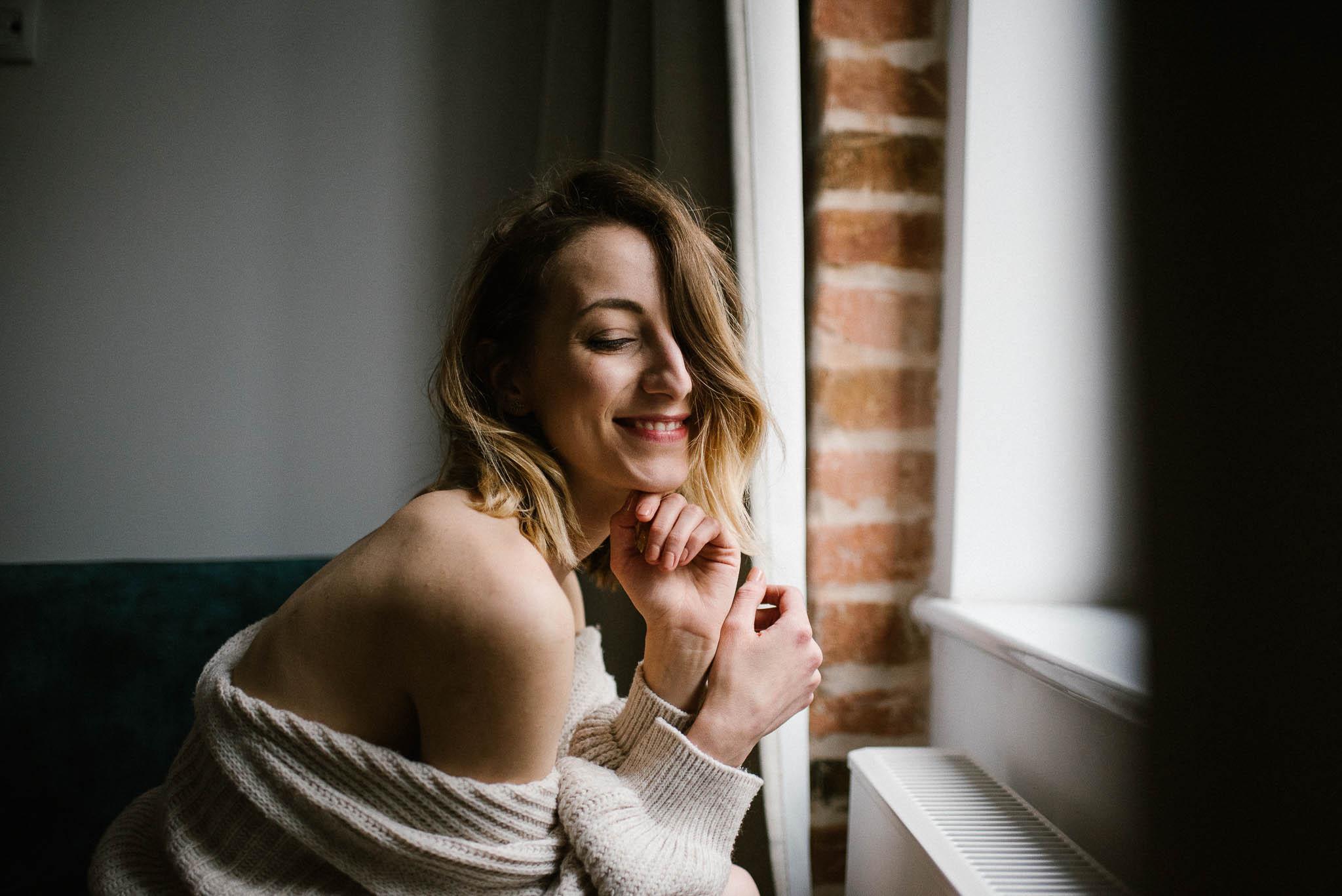 Kobieta w swetrze pokazuje ramię i siedzi przy oknie - sesja kobieca w apartamencie w Poznaniu