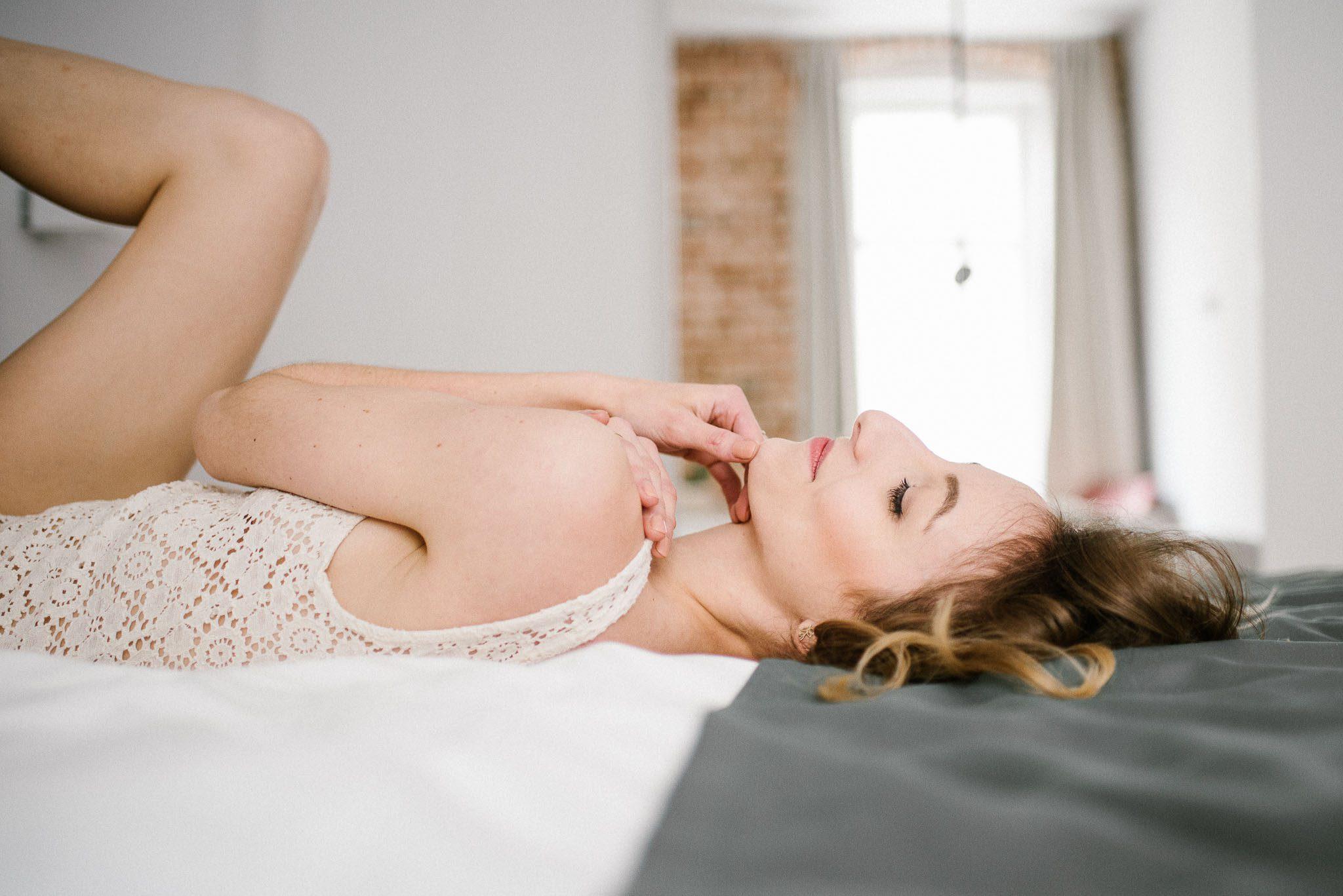 Kobieta na łóżku w bieliźnie gładzi się po dekolcie - sesja kobieca w apartamencie w Poznaniu
