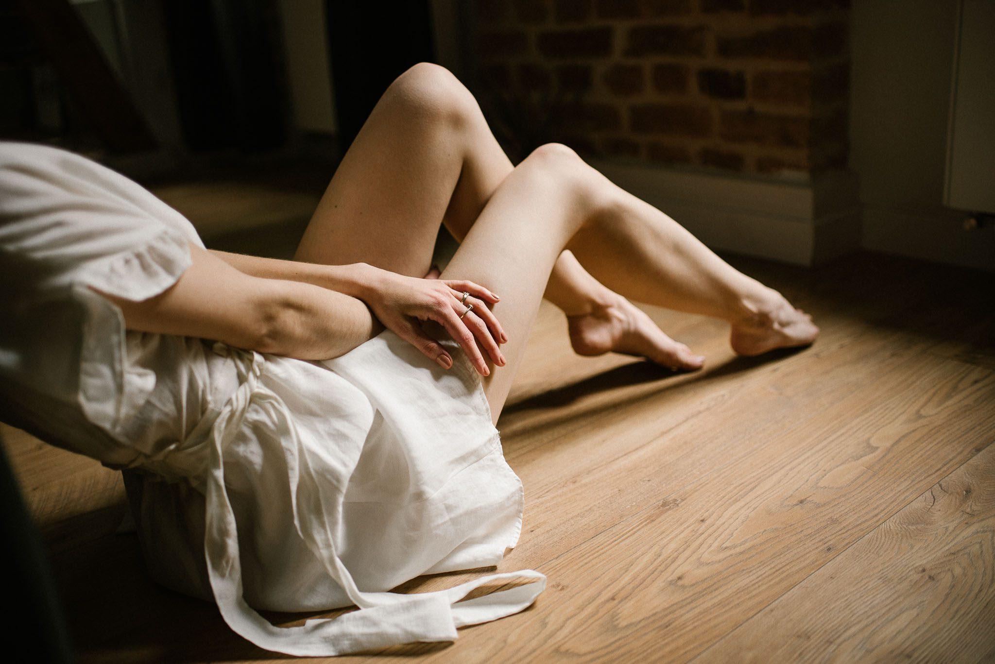 Kobieta siedzi na podłodze, zbliżenie na nogi