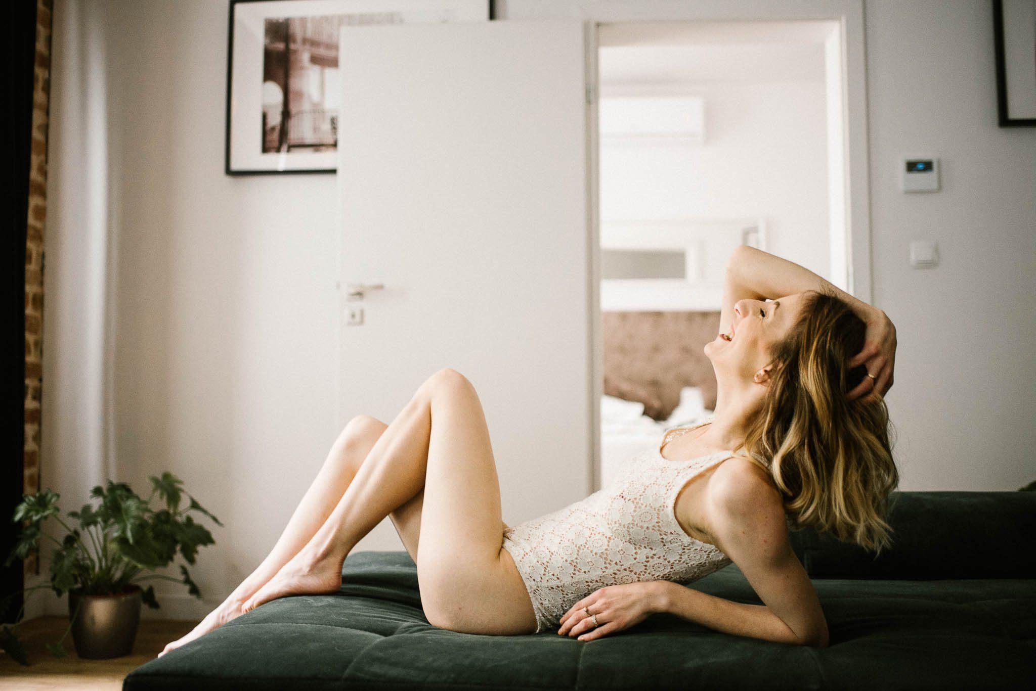 Kobieta leży w bieliźnie na kanapie - sesja kobieca w apartamencie w Poznaniu
