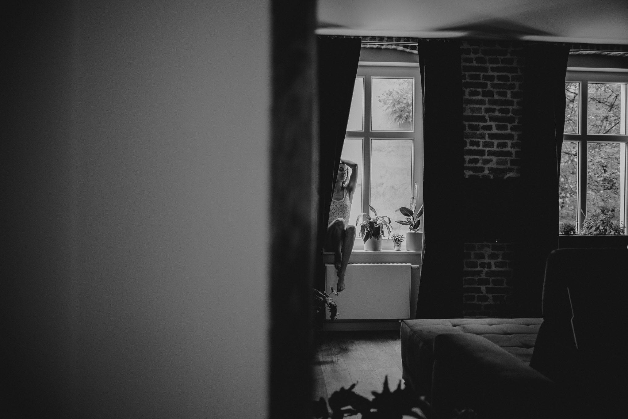 Kobieta w bieliźnie siedzi na parapecie - sesja kobieca w apartamencie w Poznaniu