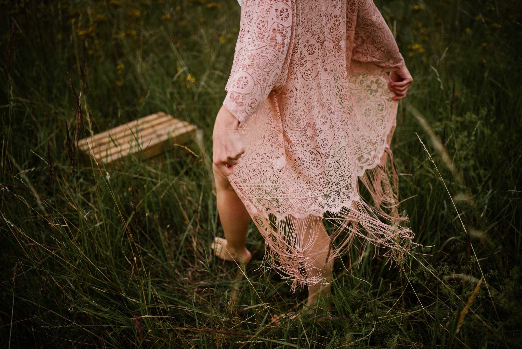 Kobieta idzie przez łąkę w stronę drewnianej skrzyni, zbliżenie na nogi - sesja kobieca sensualna w plenerze Poznań