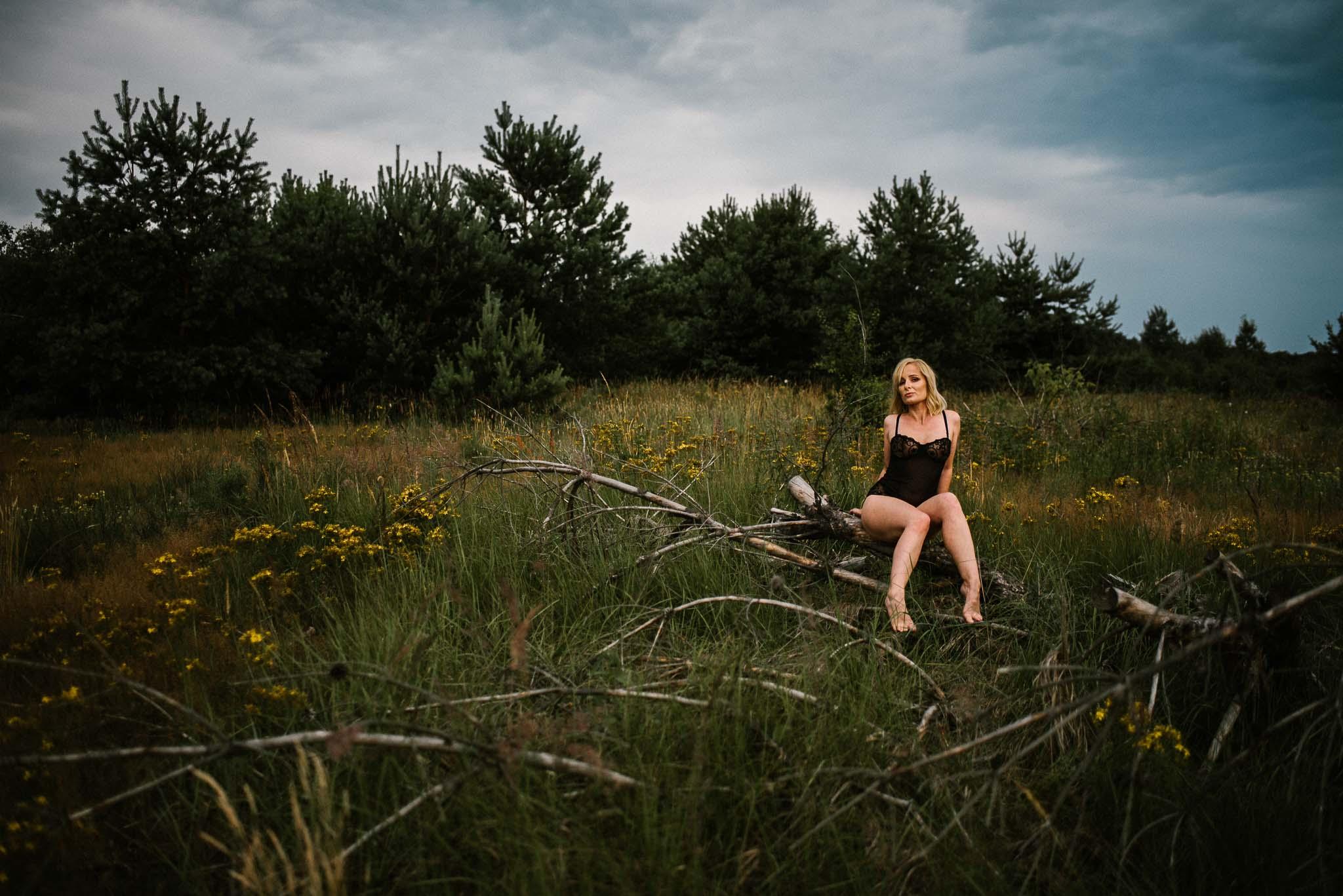 Kobieta siedzi na pniu drzewa na łące w bieliźnie - sesja kobieca sensualna w plenerze Poznań