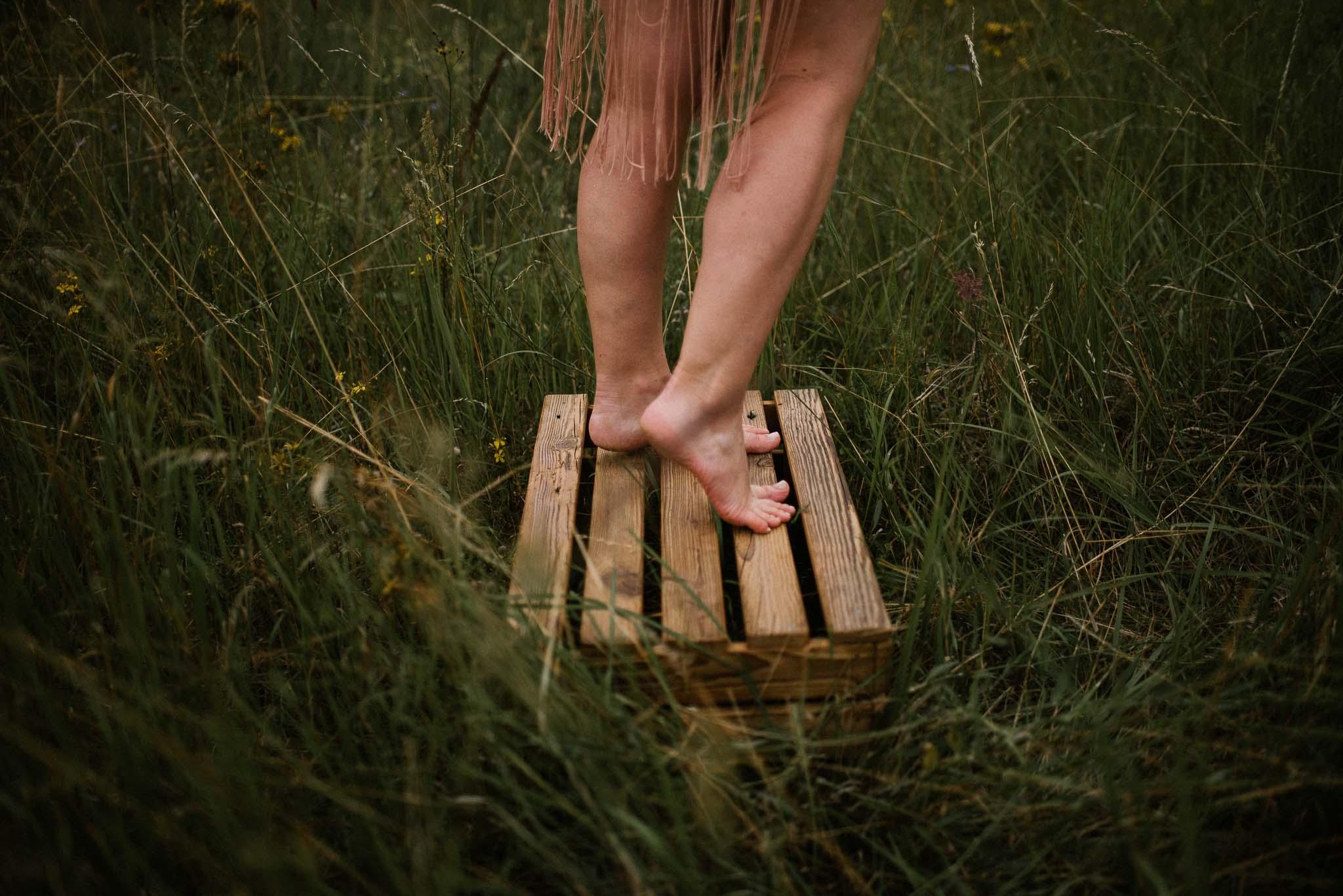 Kobieta stoi na drewnianej skrzynce na łące - sesja kobieca sensualna w plenerze Poznań