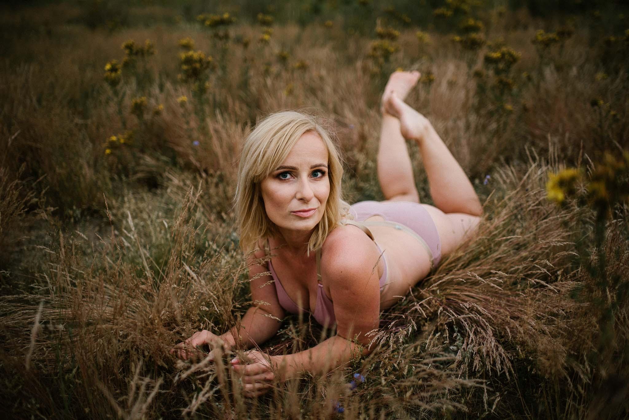 Kobieta leży w bieliźnie na łące - sesja kobieca sensualna w plenerze Poznań