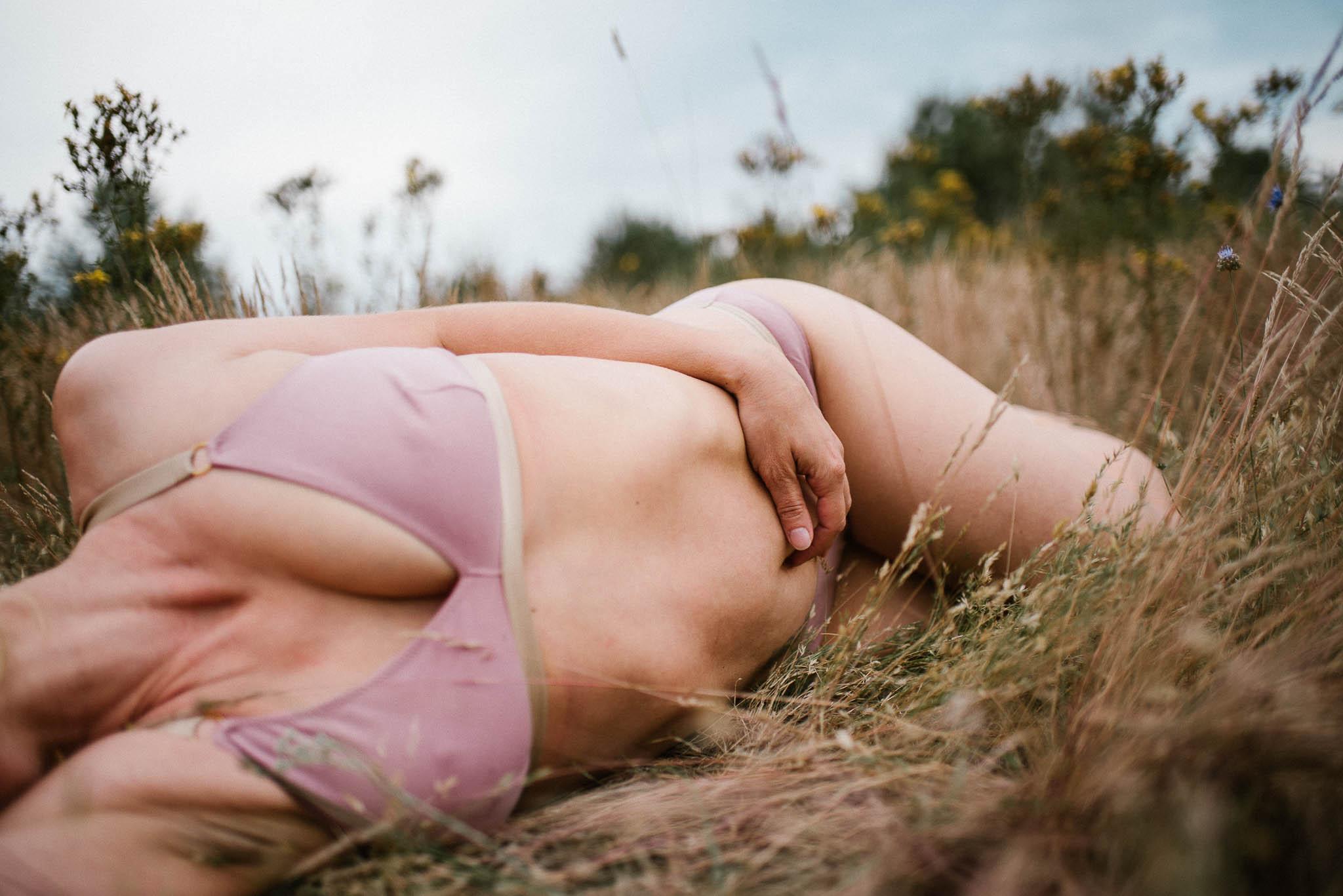 Kobieta na łące w bieliźnie się dotyka - sesja kobieca sensualna w plenerze Poznań
