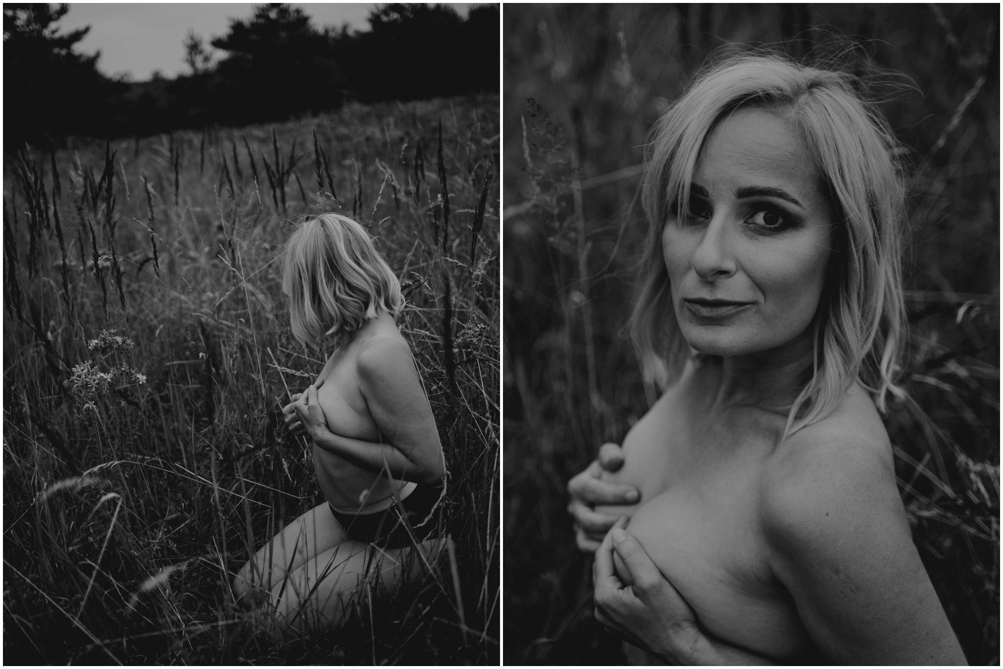 Kobieta zasłania piersi siedząc na łące - sesja kobieca sensualna w plenerze Poznań