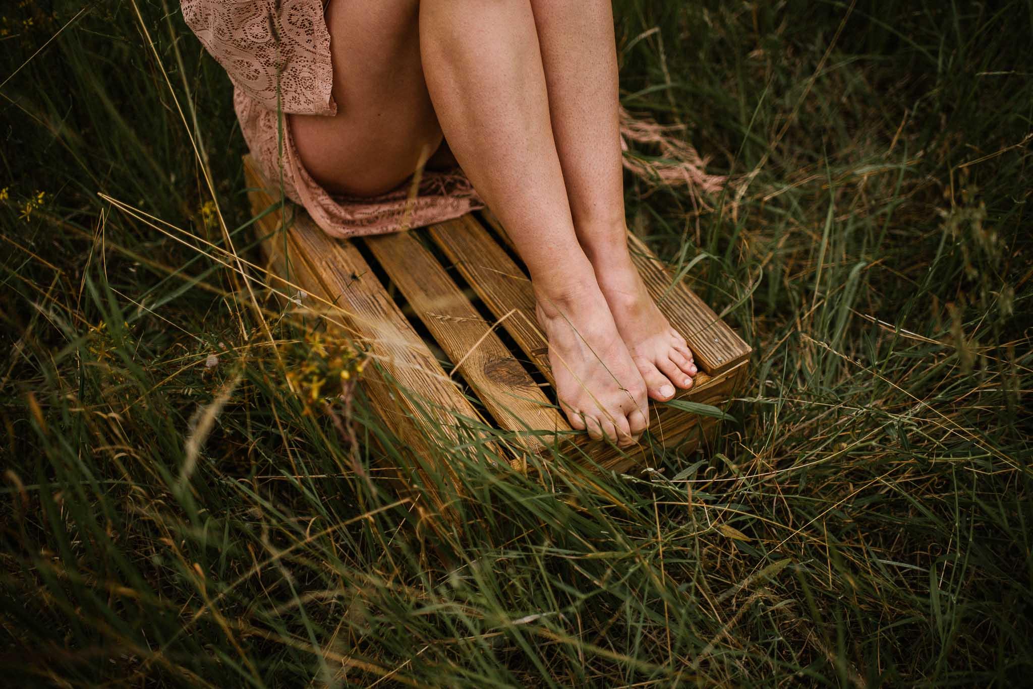 Kobieta siedzi na drewnianej skrzyni - sesja kobieca sensualna w plenerze Poznań