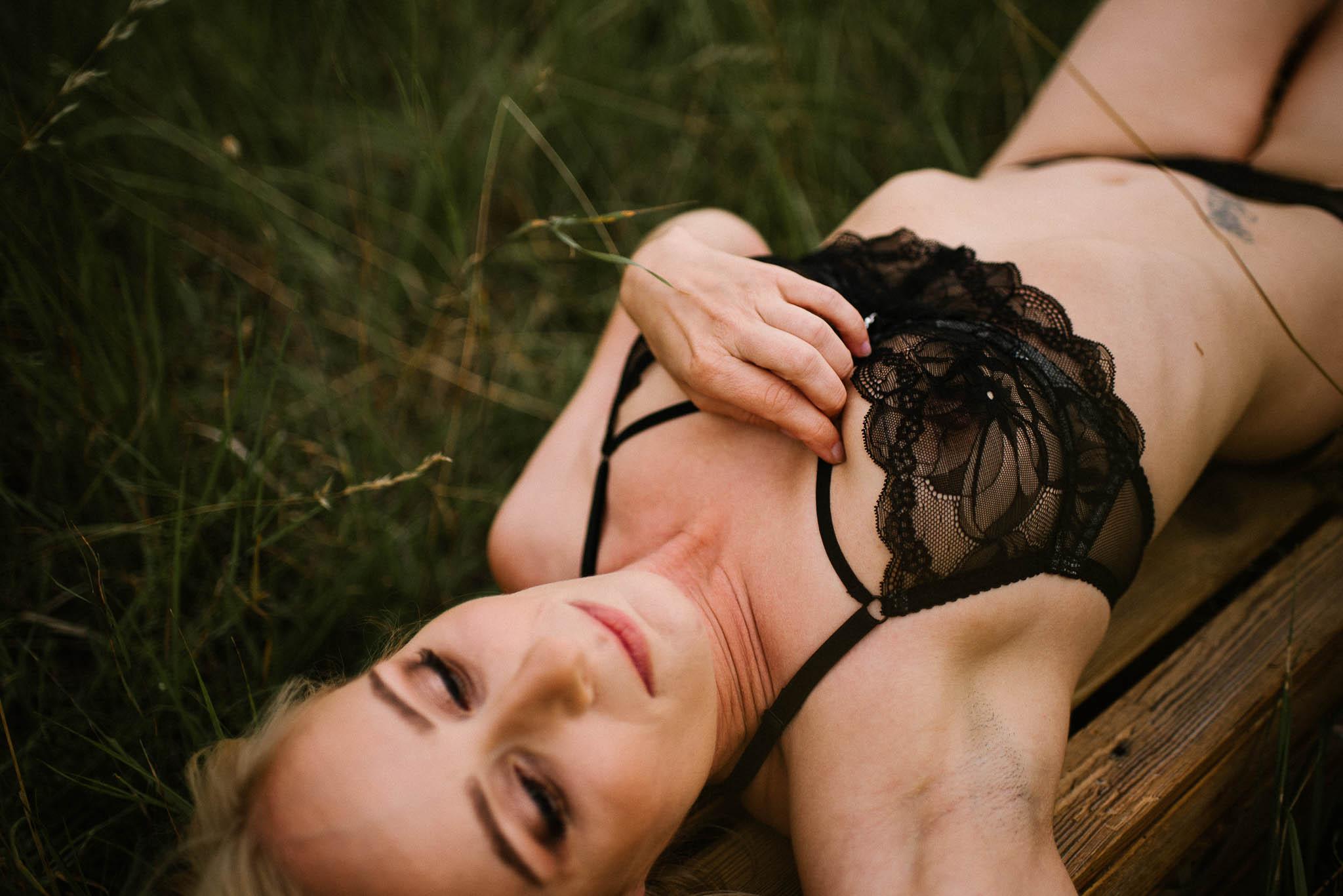 Kobieta w bieliźnie leży na łące - sesja kobieca sensualna w plenerze Poznań
