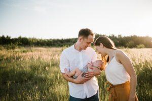Tata trzyma niemowlę na rękach, a mama na nie patrzy - sesja rodzinna w plenerze Morasko Poznań
