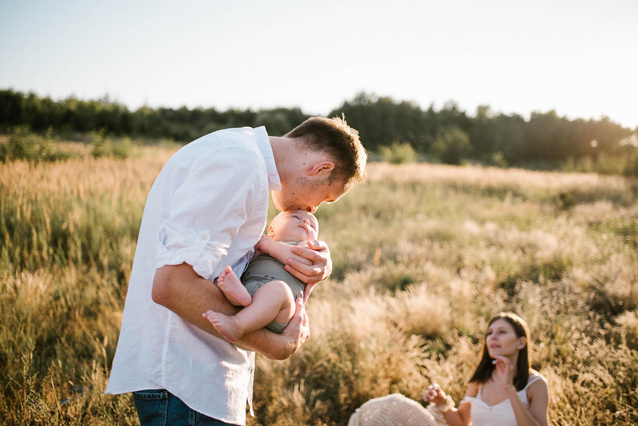 Tata podaje dziecko mamie do karmienia - sesja rodzinna w plenerze Poznań Morasko
