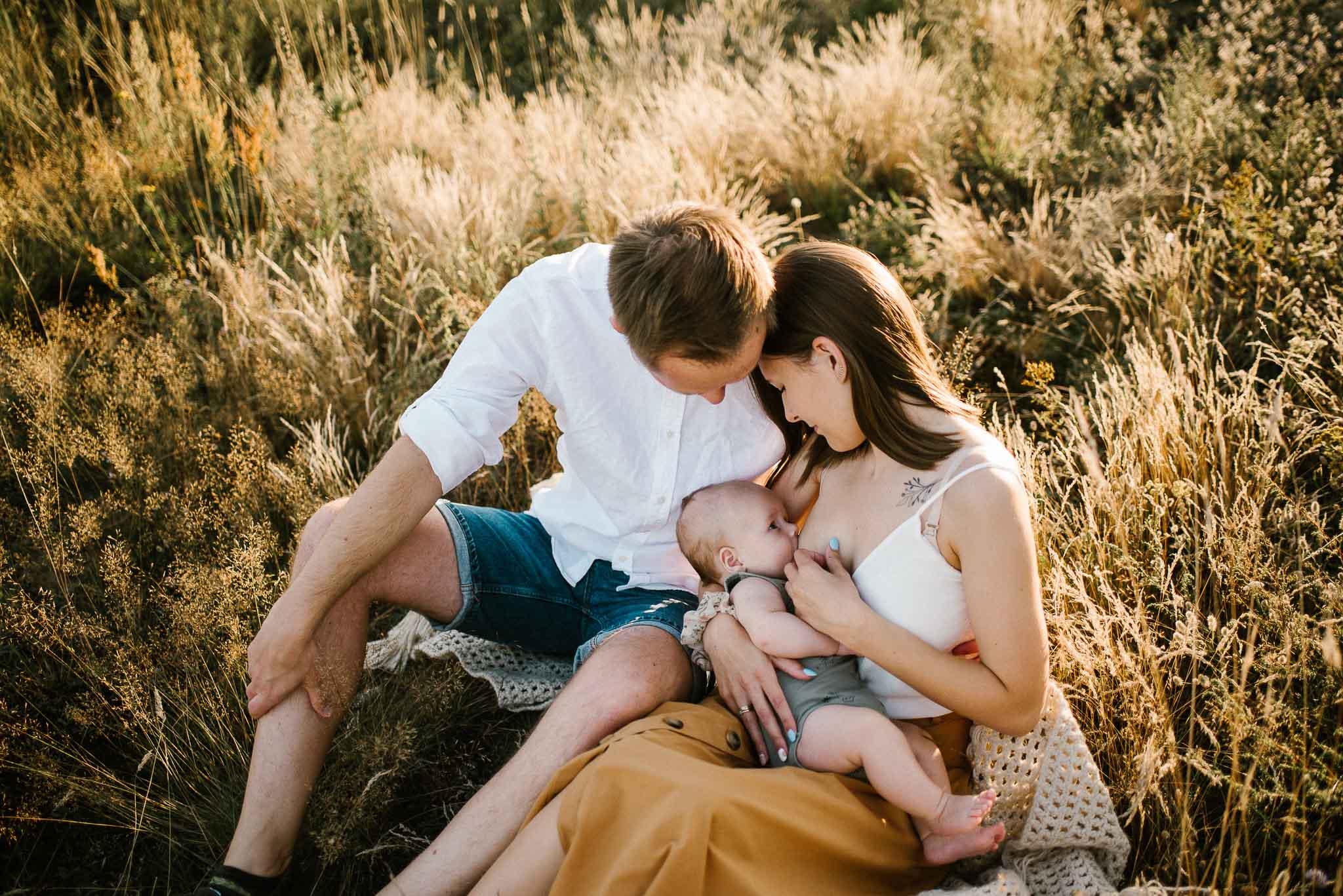 Kobieta karmi dziecko piersią siedząc na kocu - sesja rodzinna w plenerze Poznań Morasko