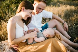 Rodzice siedzą na kocu, dziecko u mamy na kolanach - sesja rodzinna w plenerze Morasko Poznań