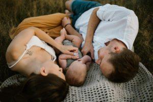 Niemowlę z rodzicami leży na kocu na łące - sesja rodzinna w plenerze Morasko Poznań