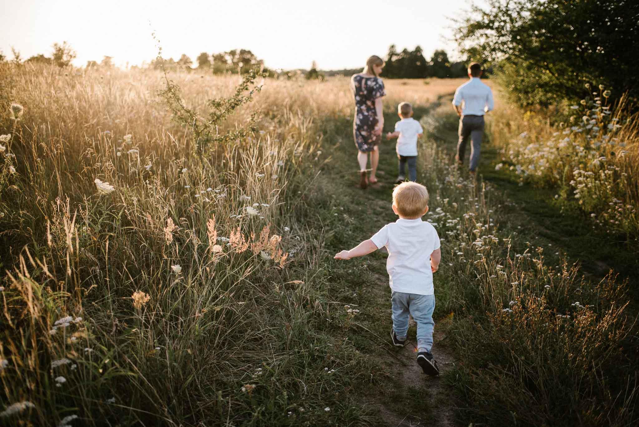 Rodzina idzie przez łąkę - sesja rodzinna w plenerze na łące w Poznaniu