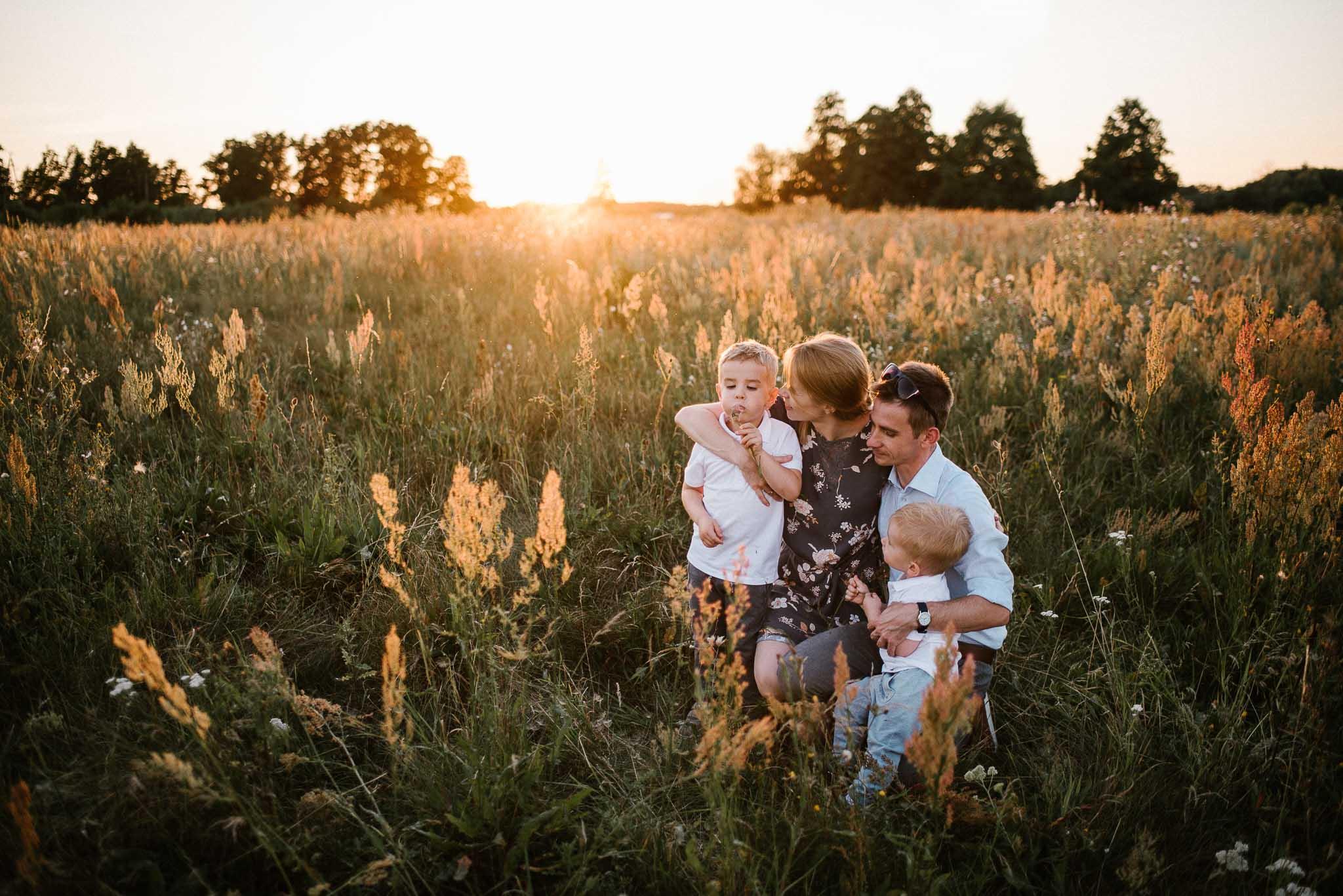 Rodzina na łące podczas zachodu słońca - sesja rodzinna w plenerze na łące w Poznaniu