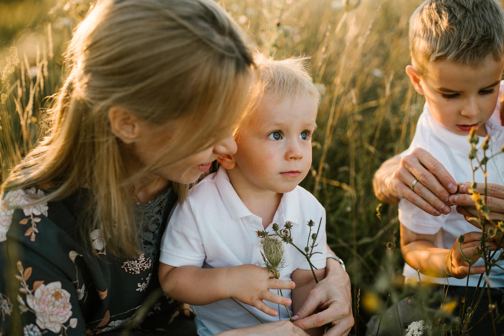 Rodzina ogląda kwiaty na łące - sesja rodzinna w plenerze na łące w Poznaniu