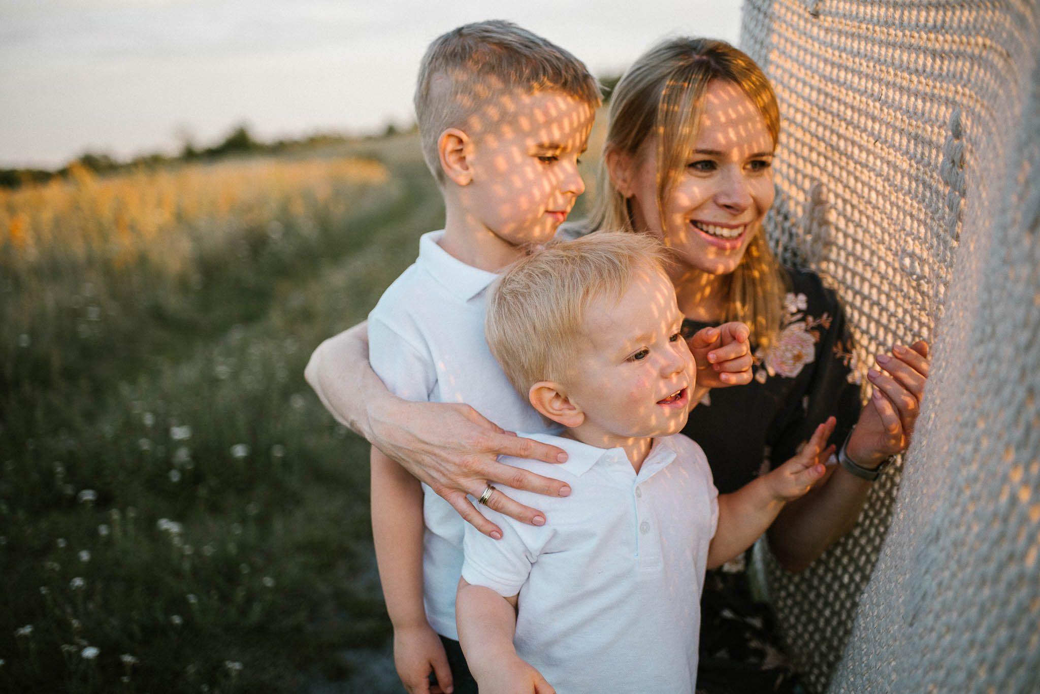 Mama z synami na łące z kocem - sesja rodzinna w plenerze na łące w Poznaniu