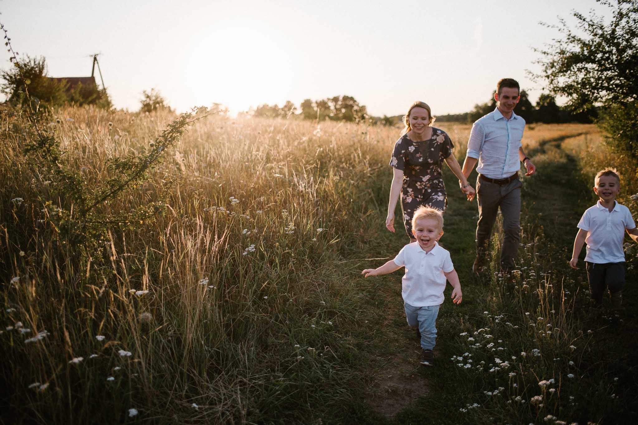 Rodzina biegnie polną drogą - sesja rodzinna w plenerze na łące w Poznaniu