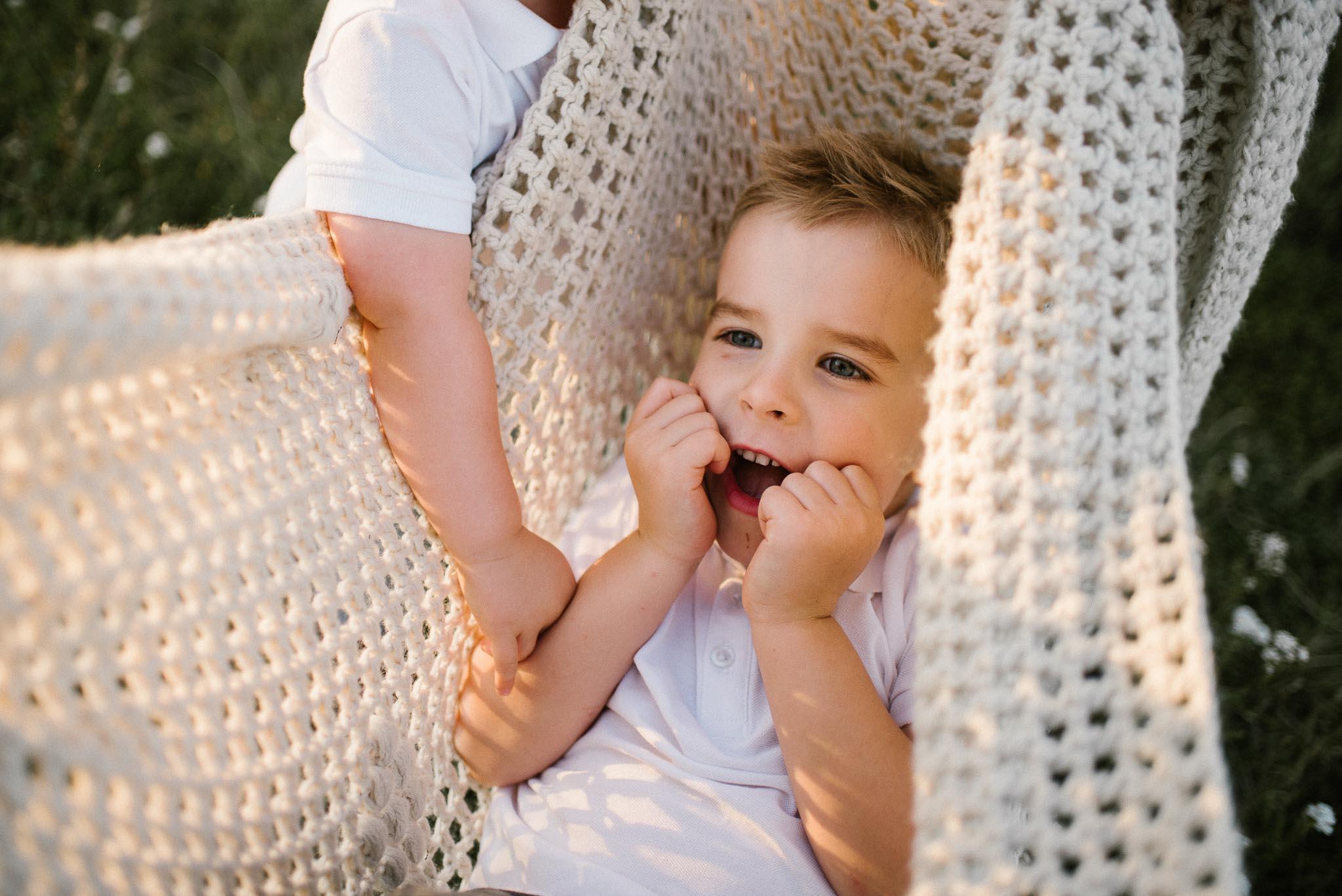 Chłopiec w hamaku z koca - sesja rodzinna w plenerze na łące w Poznaniu