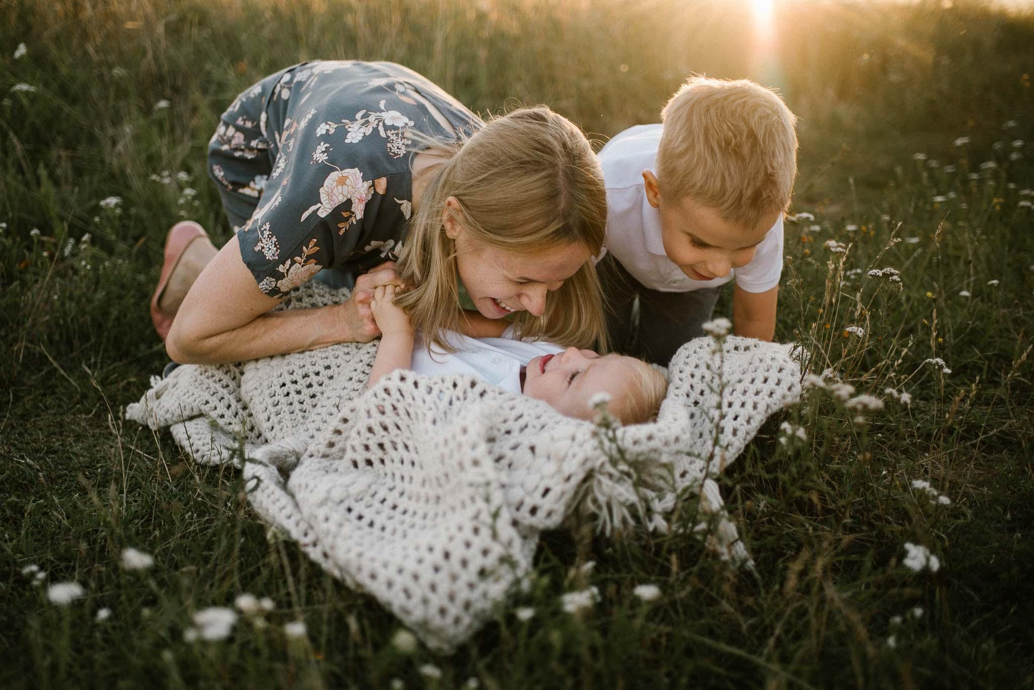 Chłopiec leży na łące na kocu - sesja rodzinna w plenerze na łące w Poznaniu