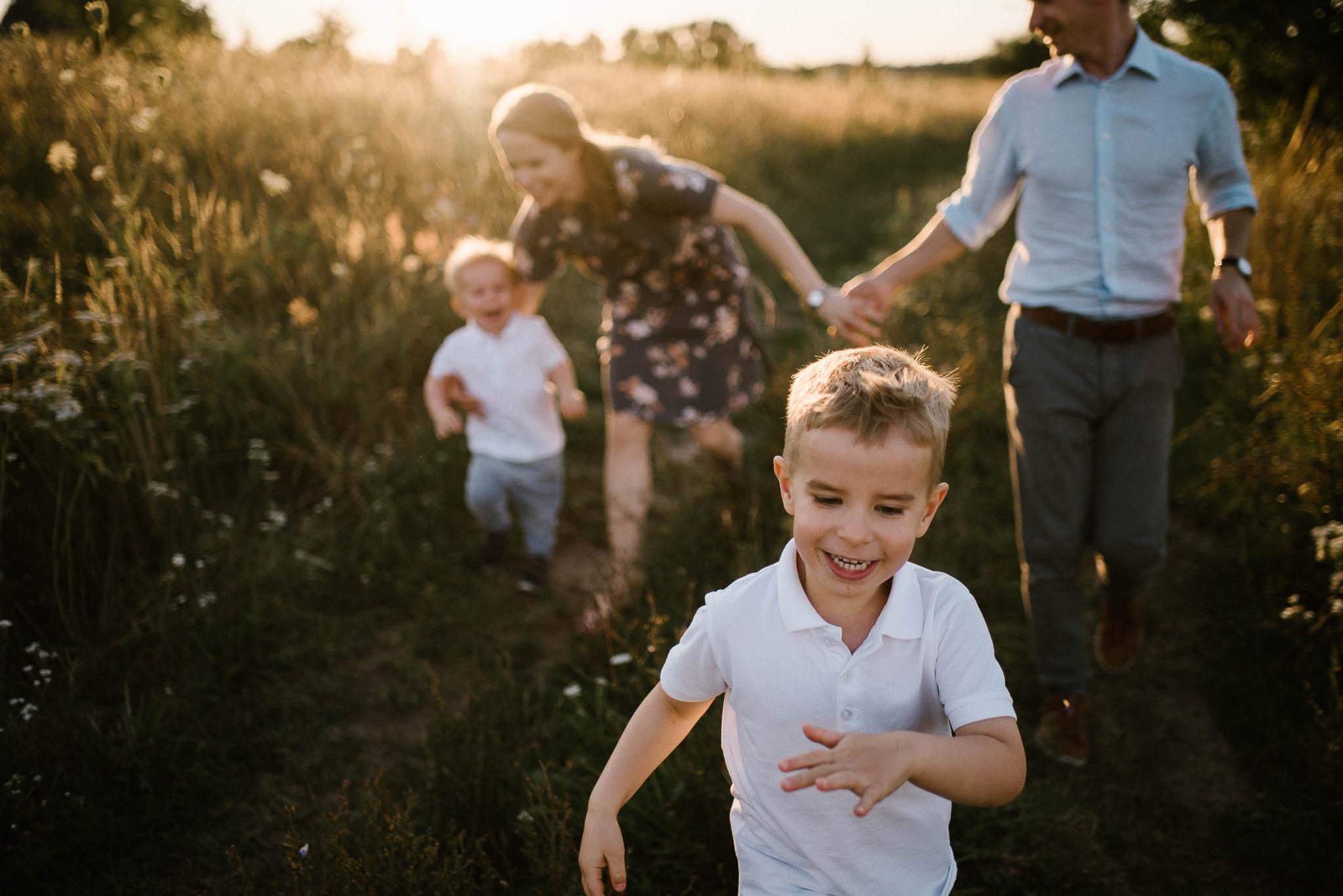Rodzina biegnie polną drogą -sesja rodzinna w plenerze na łące w Poznaniu