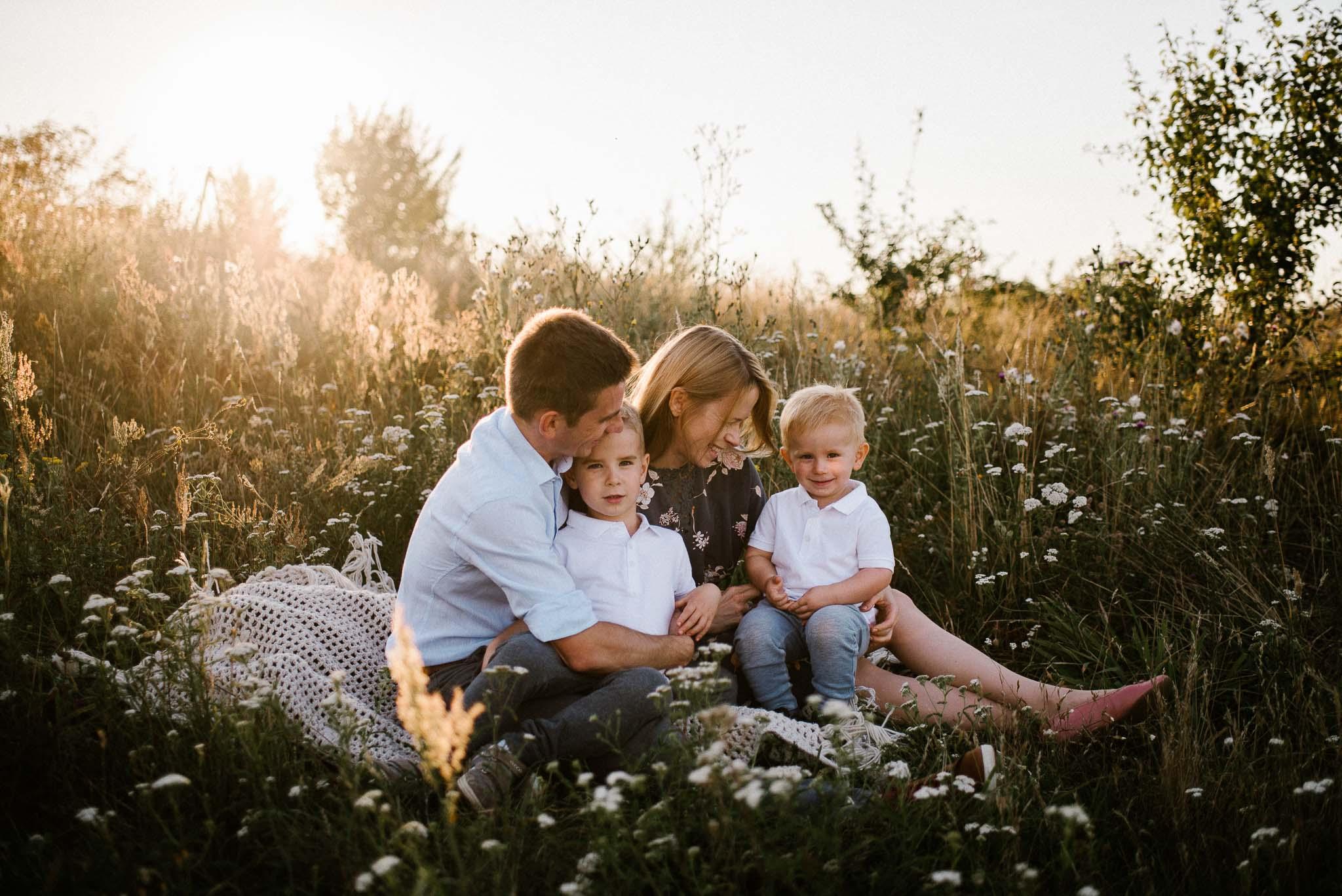 Rodzina bawi się na kocu na łące - Sesja rodzinna plenerowa Poznań
