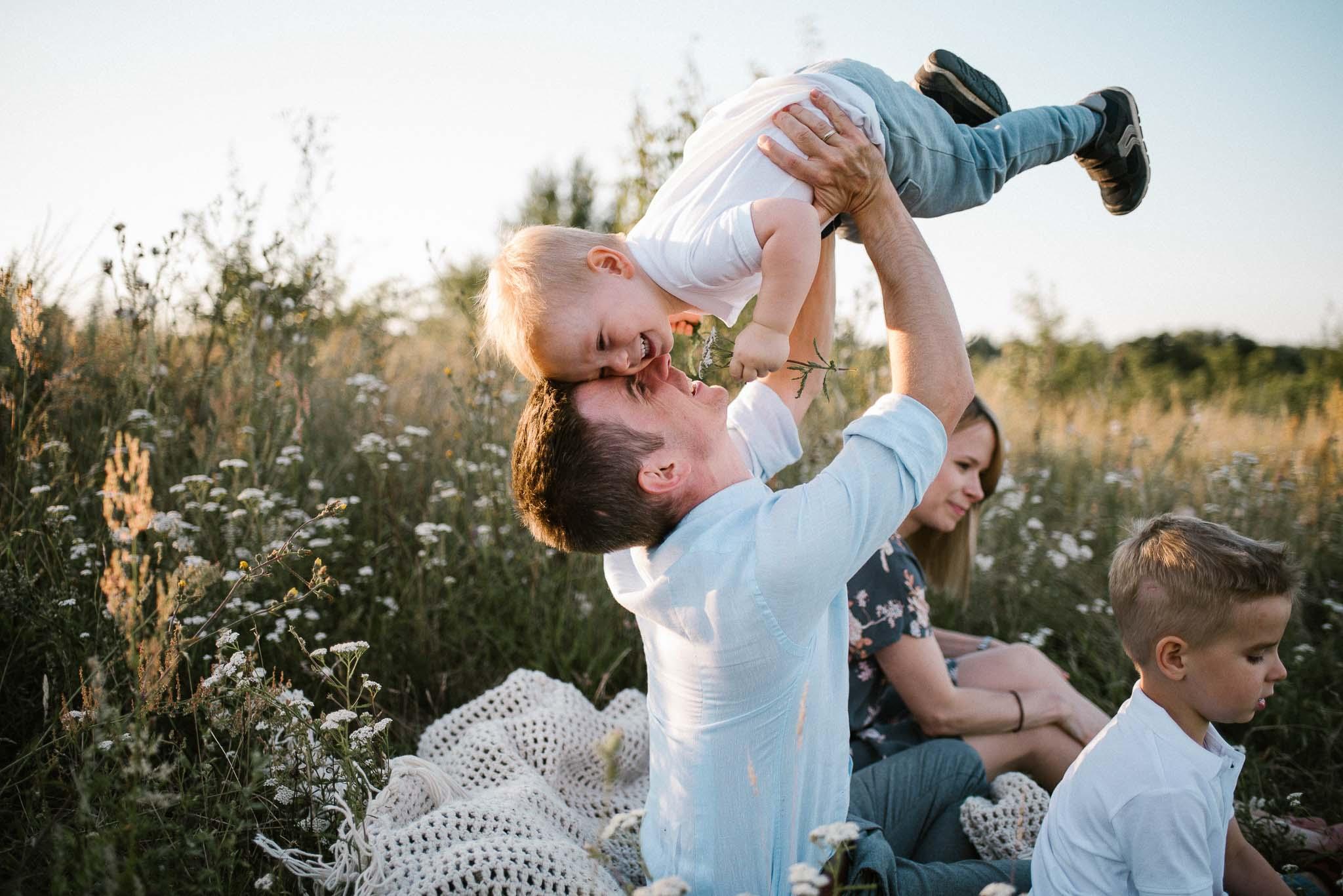 tata podrzuca syna do góry na łące - sesja rodzinna w plenerze Poznań