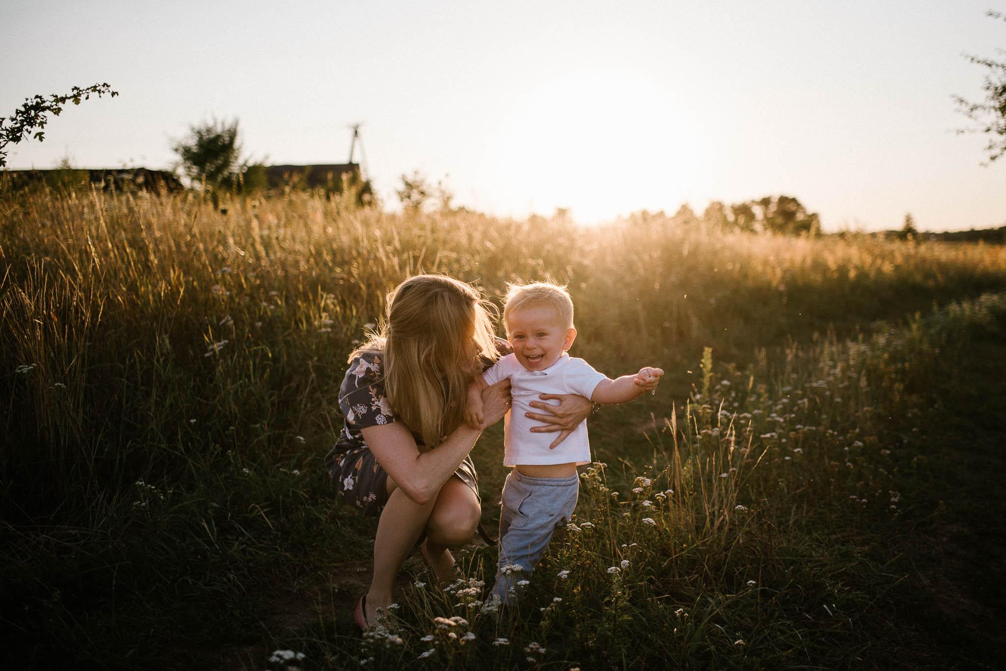 Mama złapała synka na polnej drodze - sesja rodzinna w plenerze na łące w Poznaniu