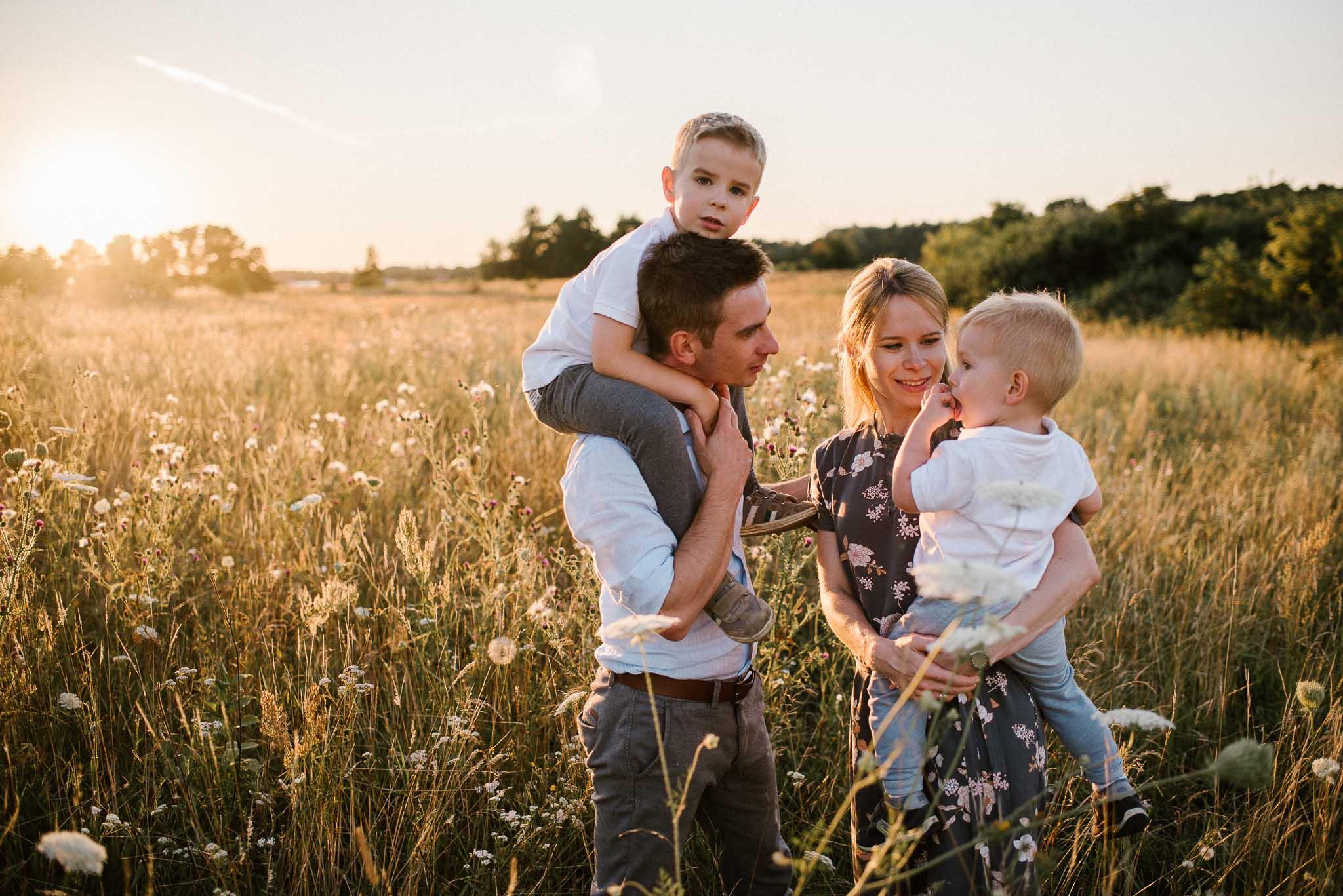 Rodzice z dziećmi na łące - sesja rodzinna w plenerze na łące w Poznaniu