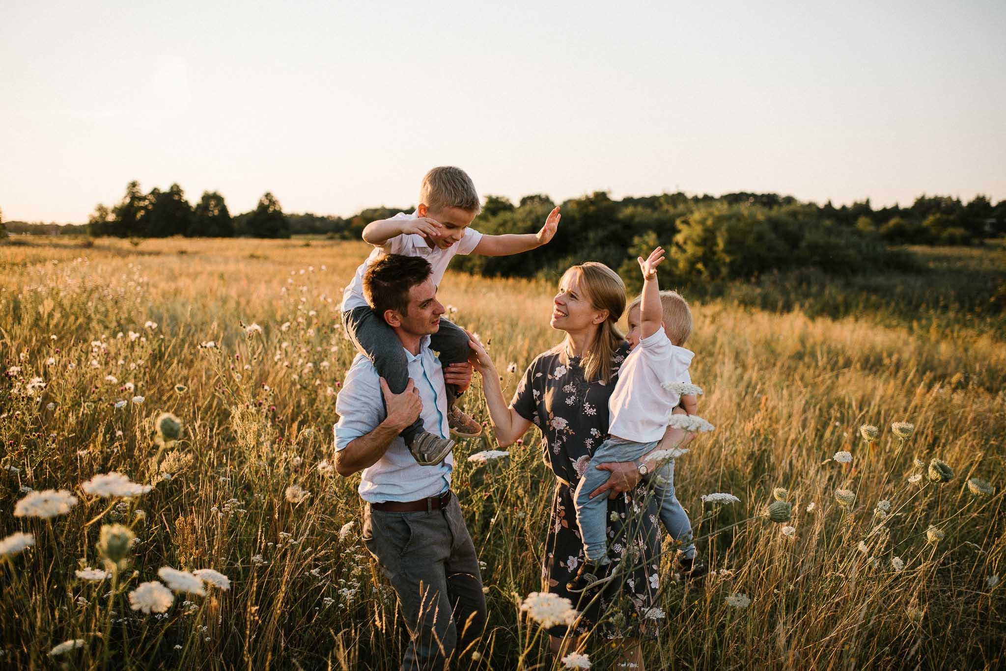 Bracia na barana u rodziców przybijają sobie piątkę - sesja rodzinna w plenerze na łące w Poznaniu