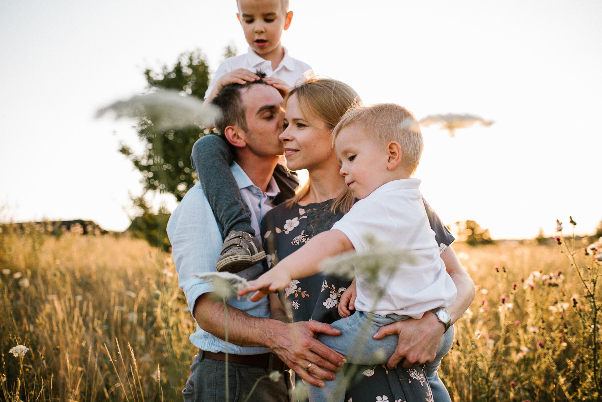 Tata daje mamie buziaka -sesja rodzinna w plenerze na łące w Poznaniu