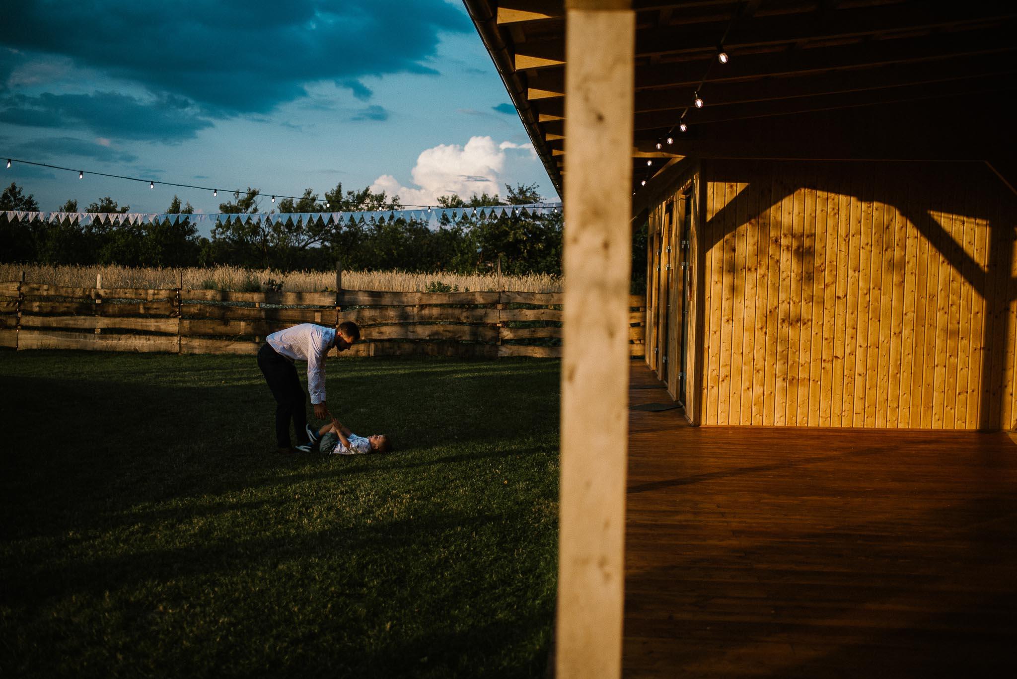 Mężczyzna bawi się z dzieckiem przy stodole - ślub w stodole Dyrkowo